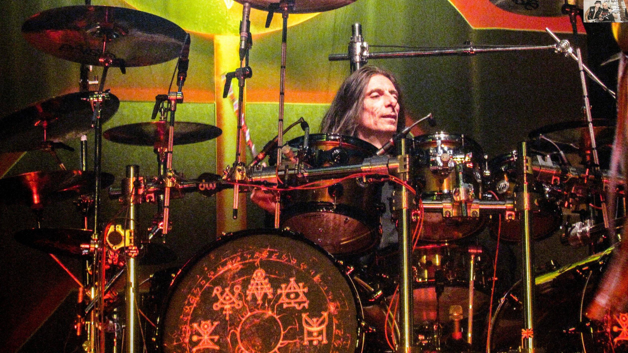 "Scott Travis mans the drums on second song ""Running Wild."""