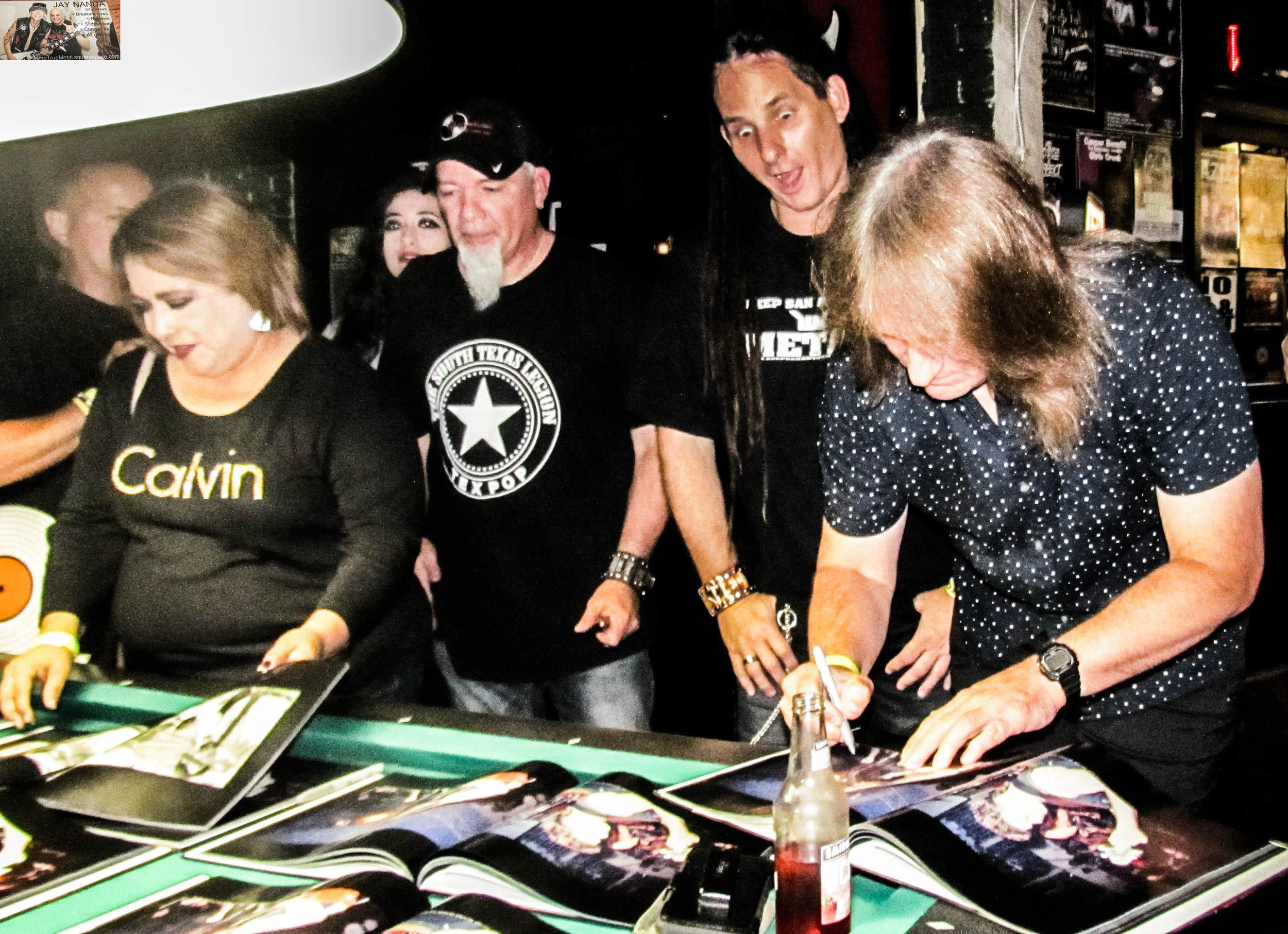 Even In Death singer Sean Nations expresses his amazement as Ron Jarzombek signs a picture of himself.