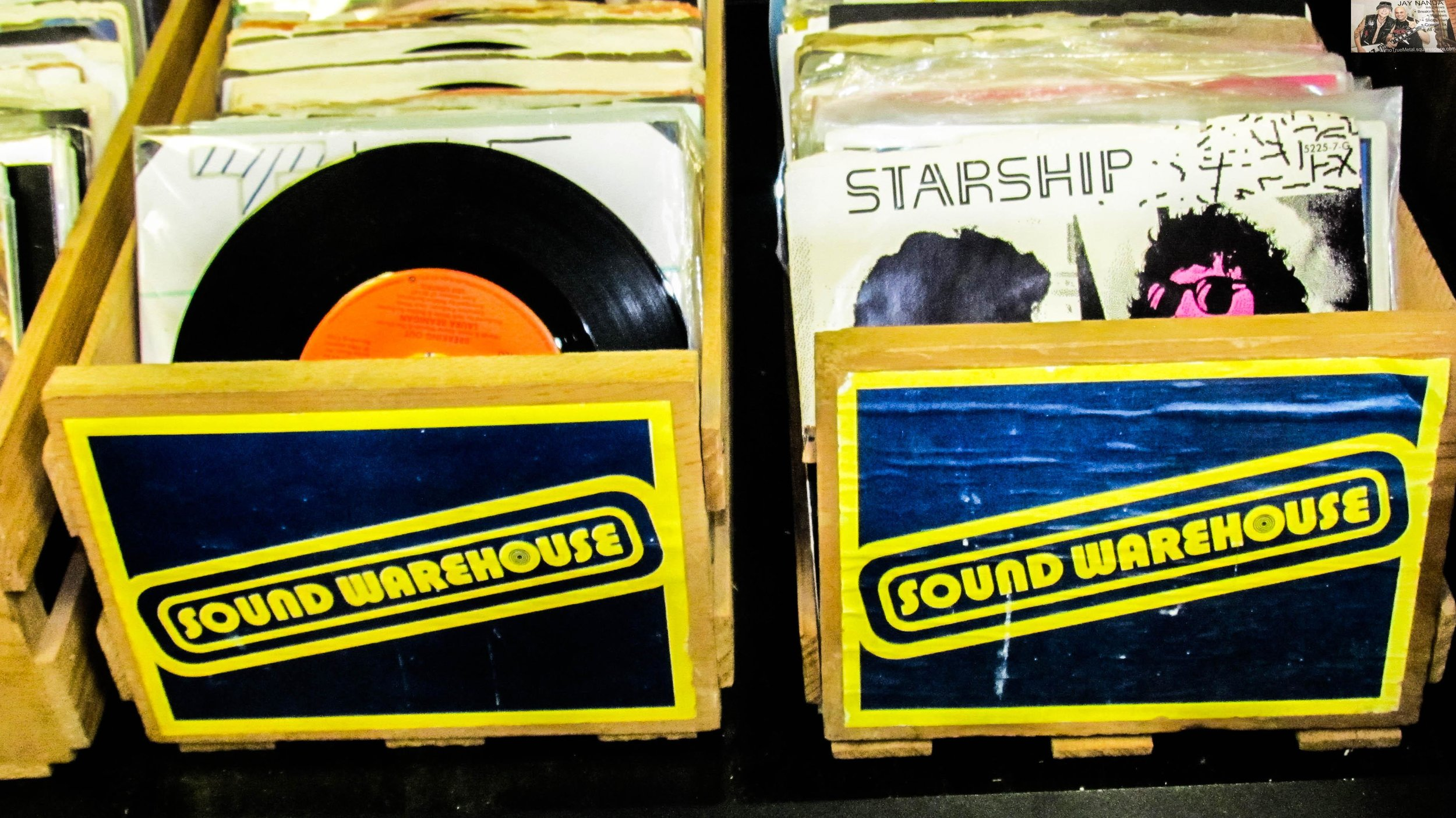 """A series of """"45"""" records of various genres sit in wooden crates labeled with a record store of their generation."""