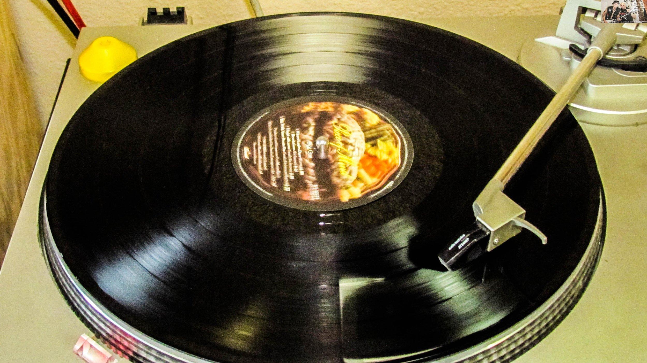 "Iron Maiden's ""Piece of Mind"" spins on vinyl between acts."