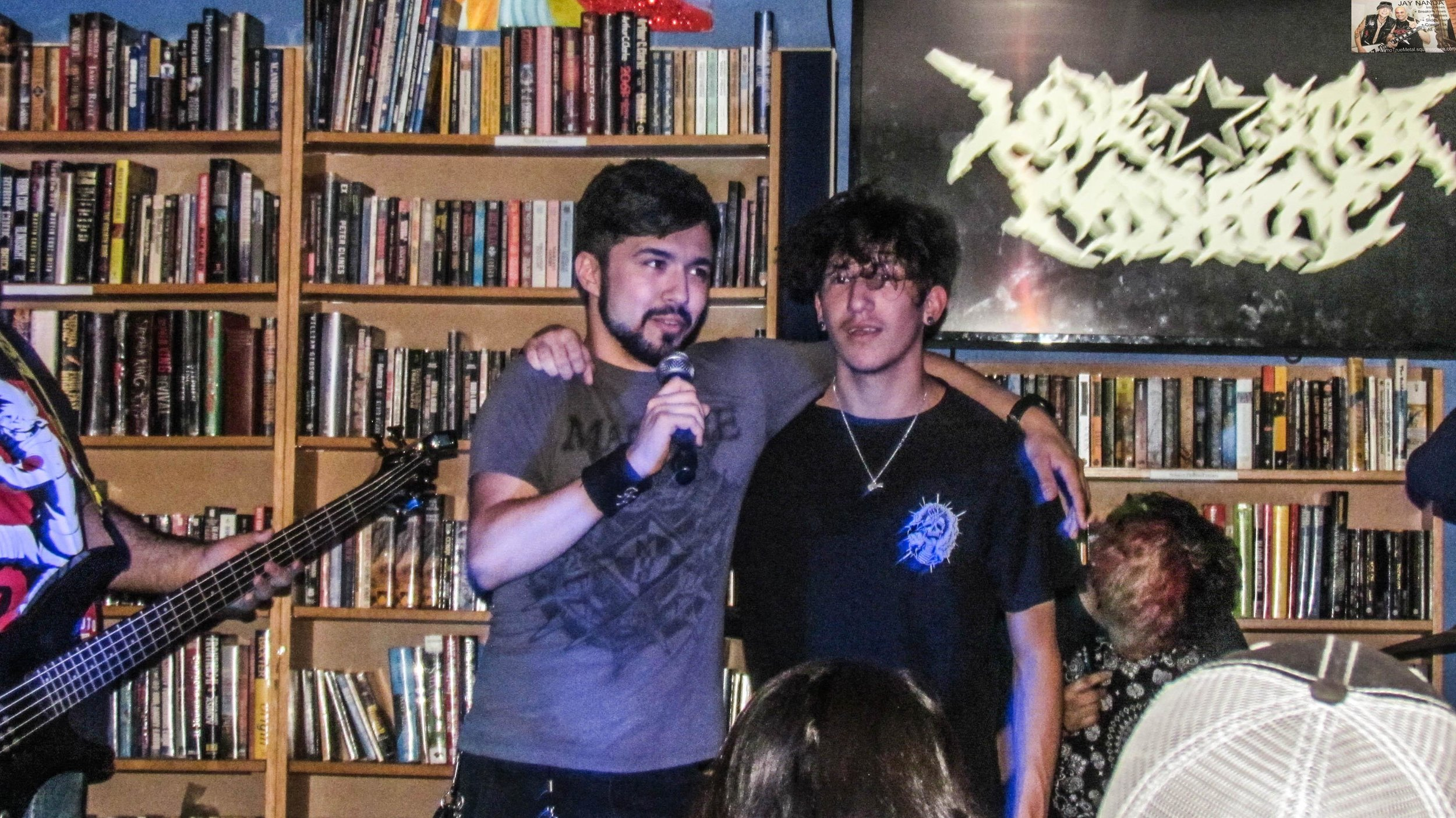Send Help bassist/vocalist Camron Maldonado (left) tells the patrons of how Lonestar Massacre vocalist Hondo Hernandez (right) inadvertently broke the neck of his Les Paul guitar as the two bands were on tour together . . .