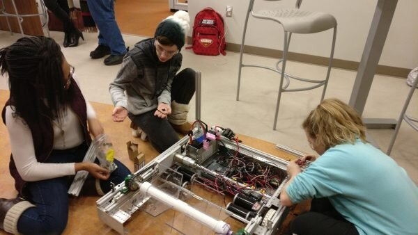 Girls on Fire team members work on constructing their robot.