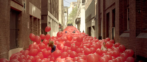 Balloons fill a city alley - Vodafone Like a Child Television commercial