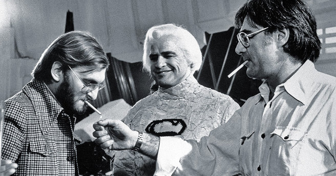 Richard Donner considers punching Pierre Spengler in the nose with his lighter as Marlon Brando looks on in glee.