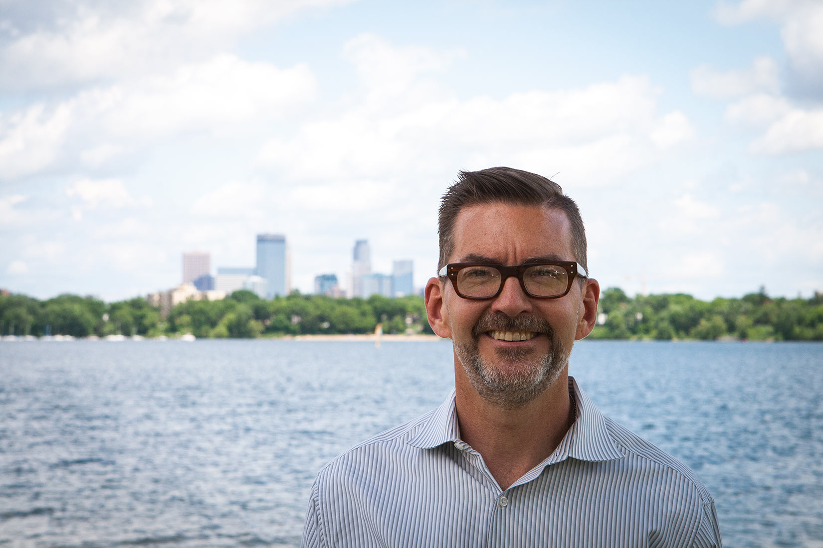 Closeup photograph of Scott Dibble in summertime with Minneapolis skyline in the background