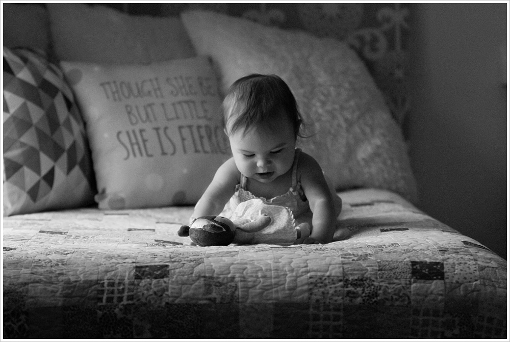 baby with doll on bed | lifestyle family photography in Cedar Park, Texas | Jason & Melaina Photography