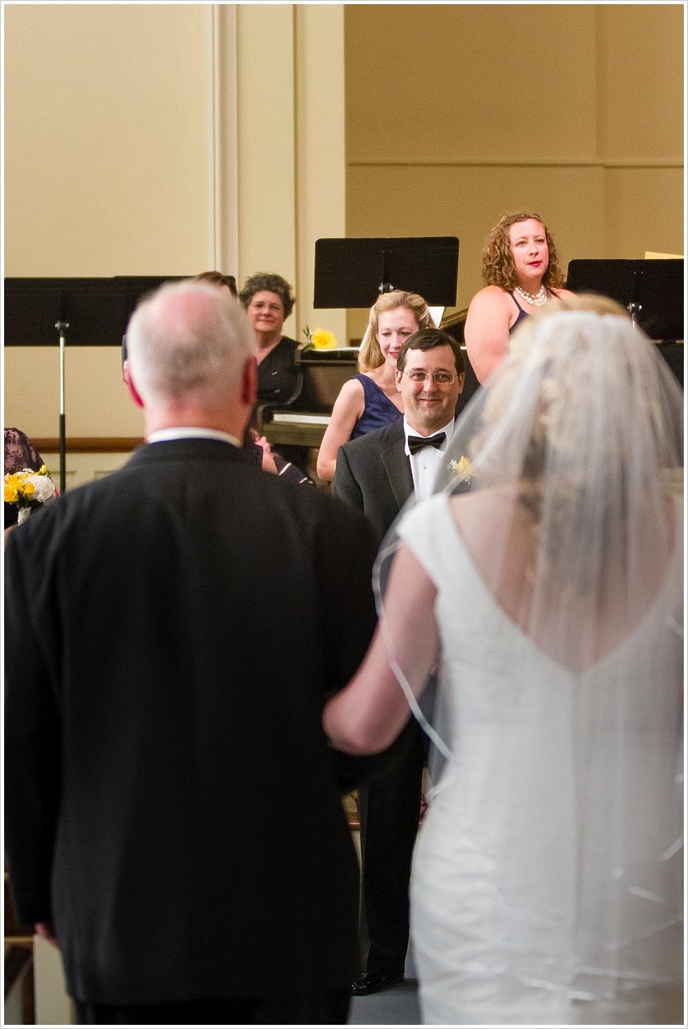 groom over bride's shoulder as she comes down the aisle | Calvary Baptist Church, Waco, TX | Jason & Melaina Photography