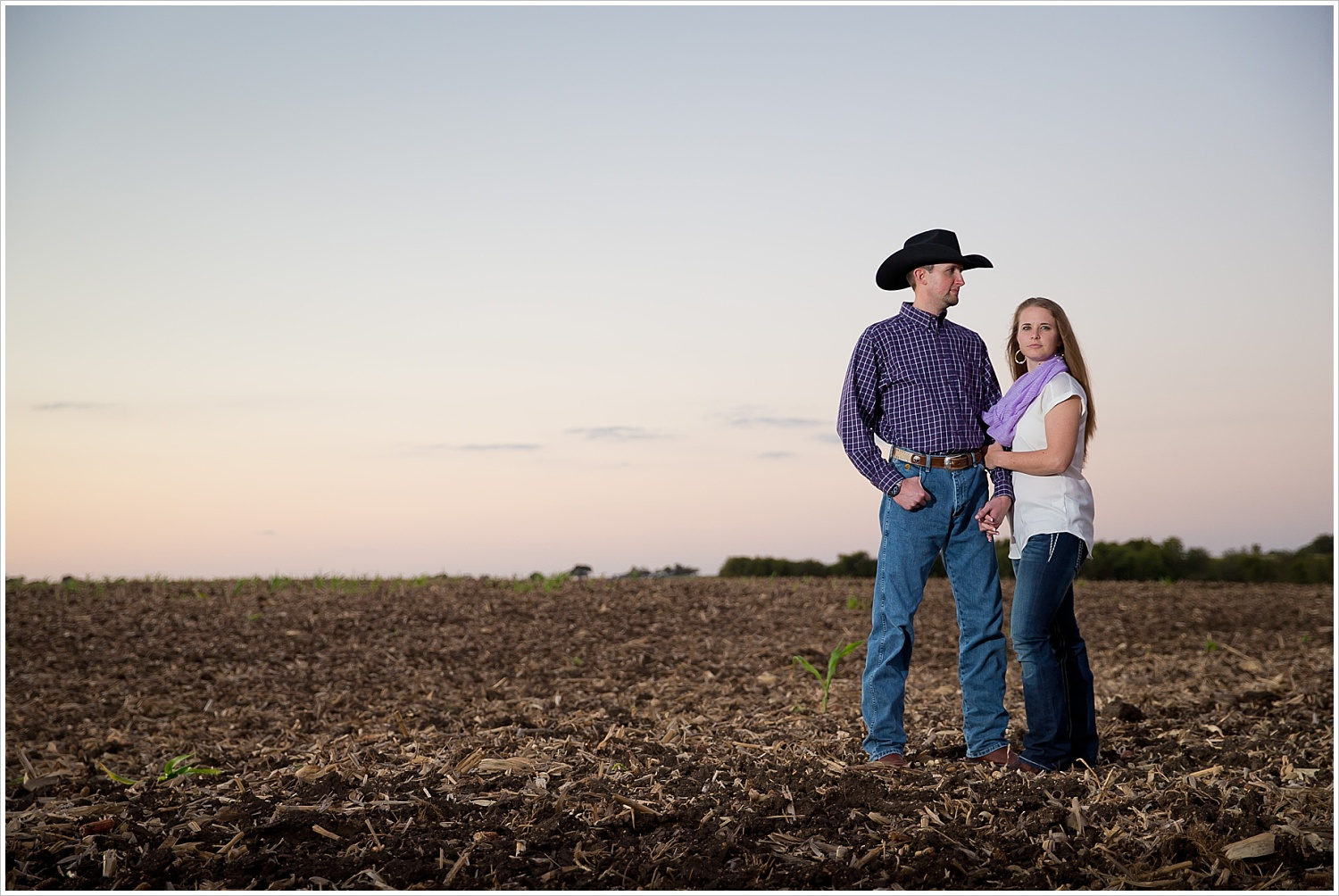 a couple posed in an open field with a sunset behind them | West, Texas | Jason & Melaina Photography