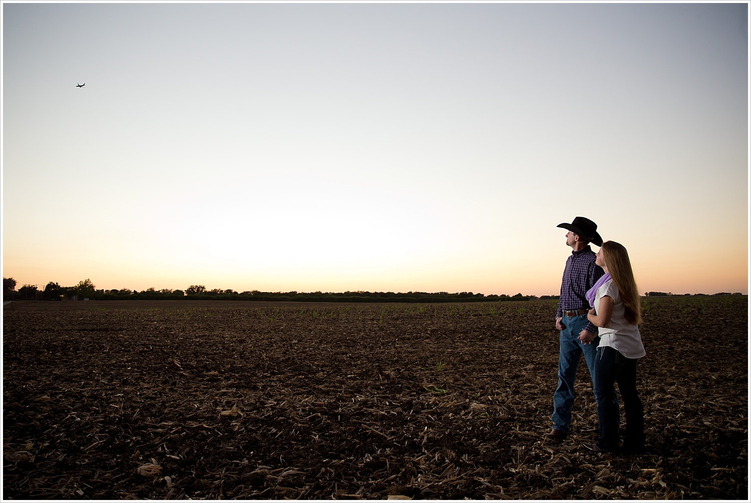 a couple watch an airplane fly over them | West, Texas Engagement Portraits | Jason & Melaina Photography