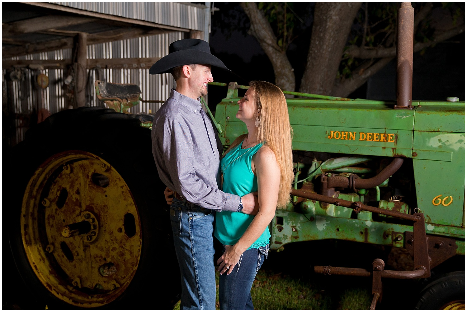 a couple embraces in front of a John Deere tractor | West, Texas Engagement Portraits | Jason & Melaina Photography