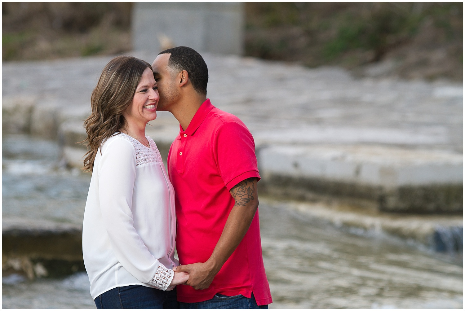 Fiance whispers into bride-to-be's ear during engagement portraits