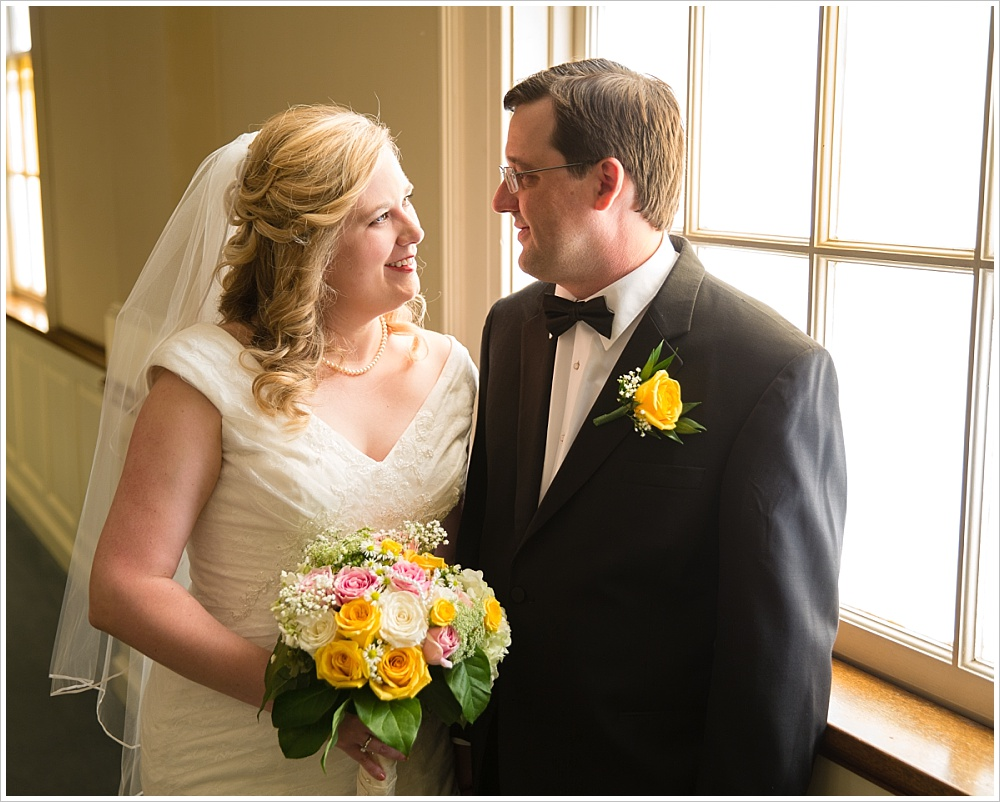 Bride and groom embrace by window after Calvary Baptist church wedding