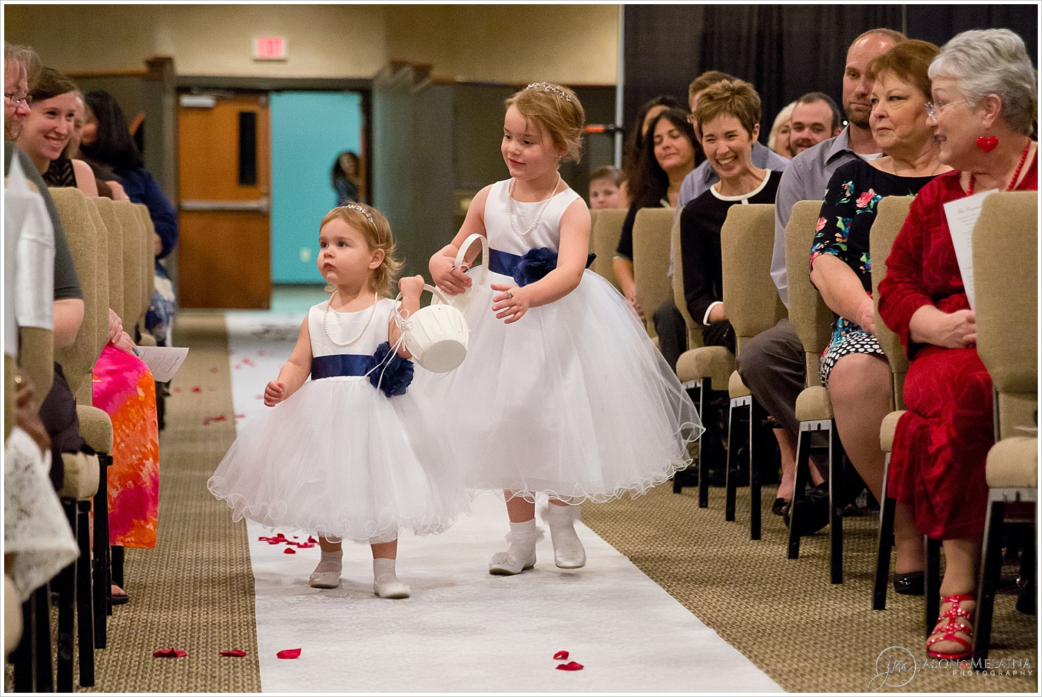 Young flower girls dressed in white dresses with navy bows walk down the aisle