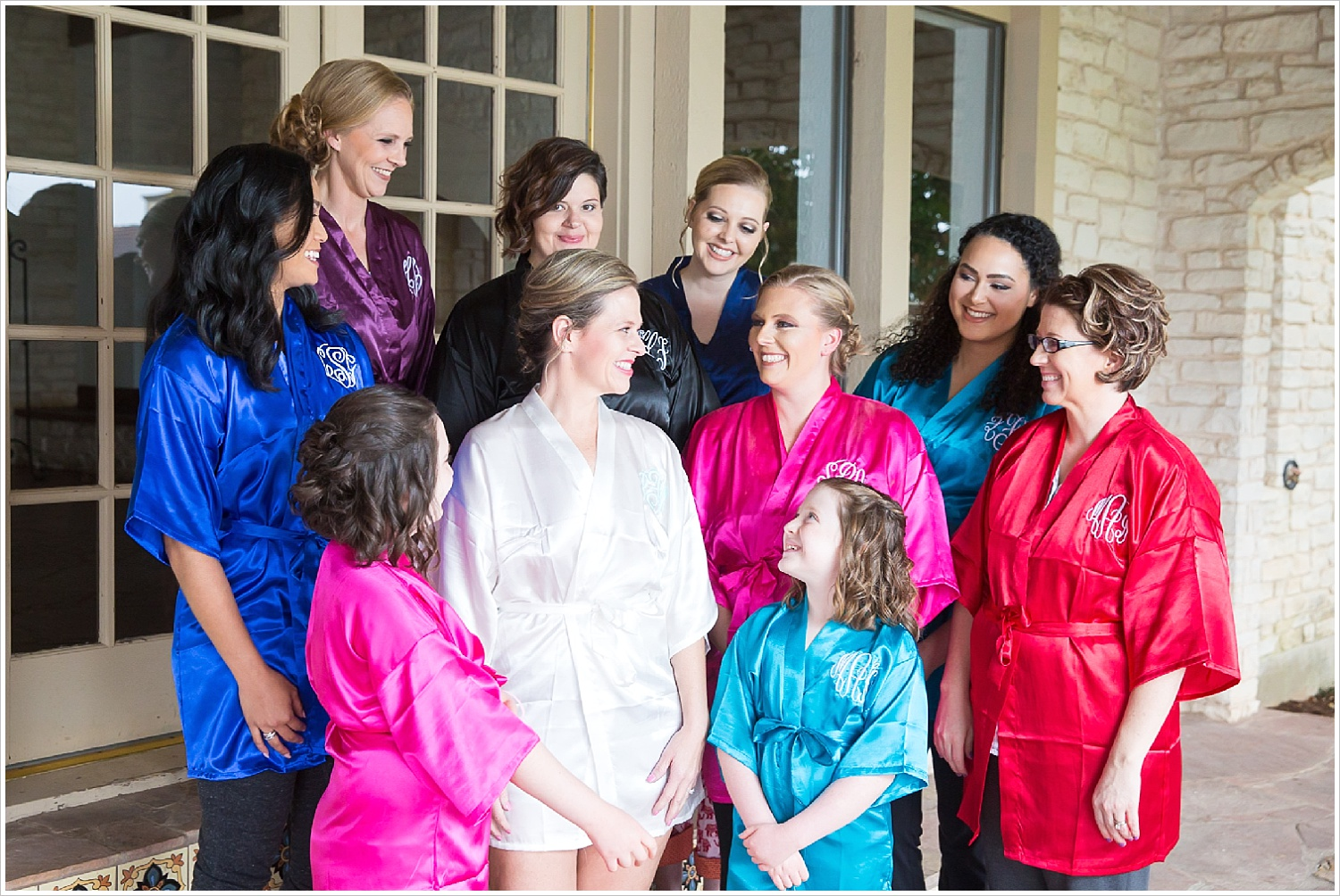 Bride and bridesmaids in monogrammed robes prior to wedding ceremony