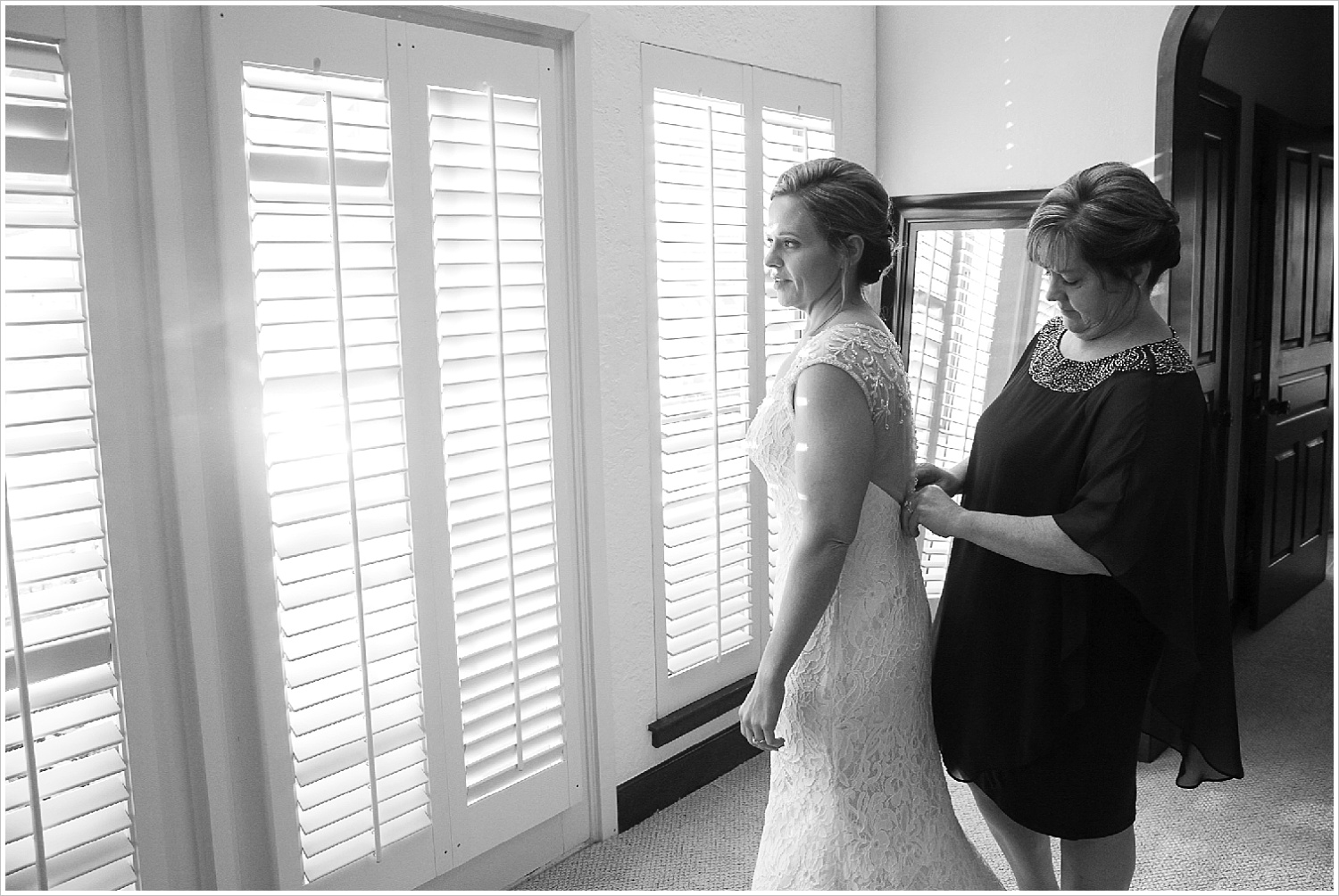 Mother buttoning up back of her daughter's wedding dress in bridal suite at La Rio Mansion