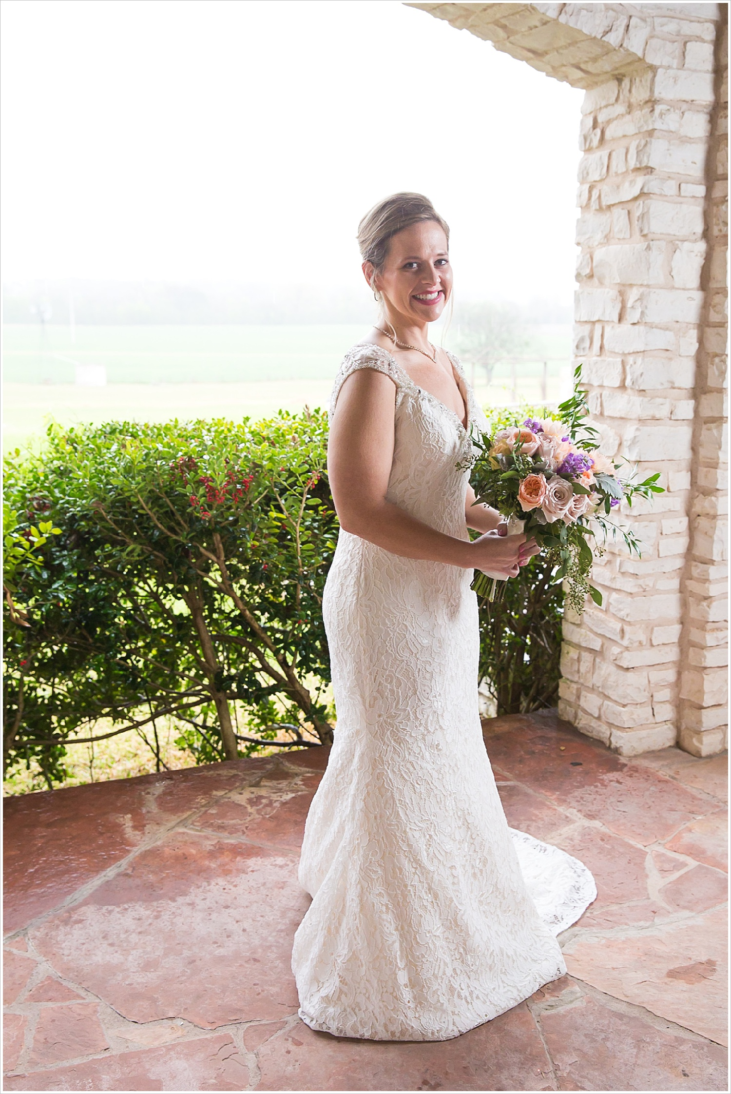 Bride stands under covered porch during rain storm at La Rio Mansion