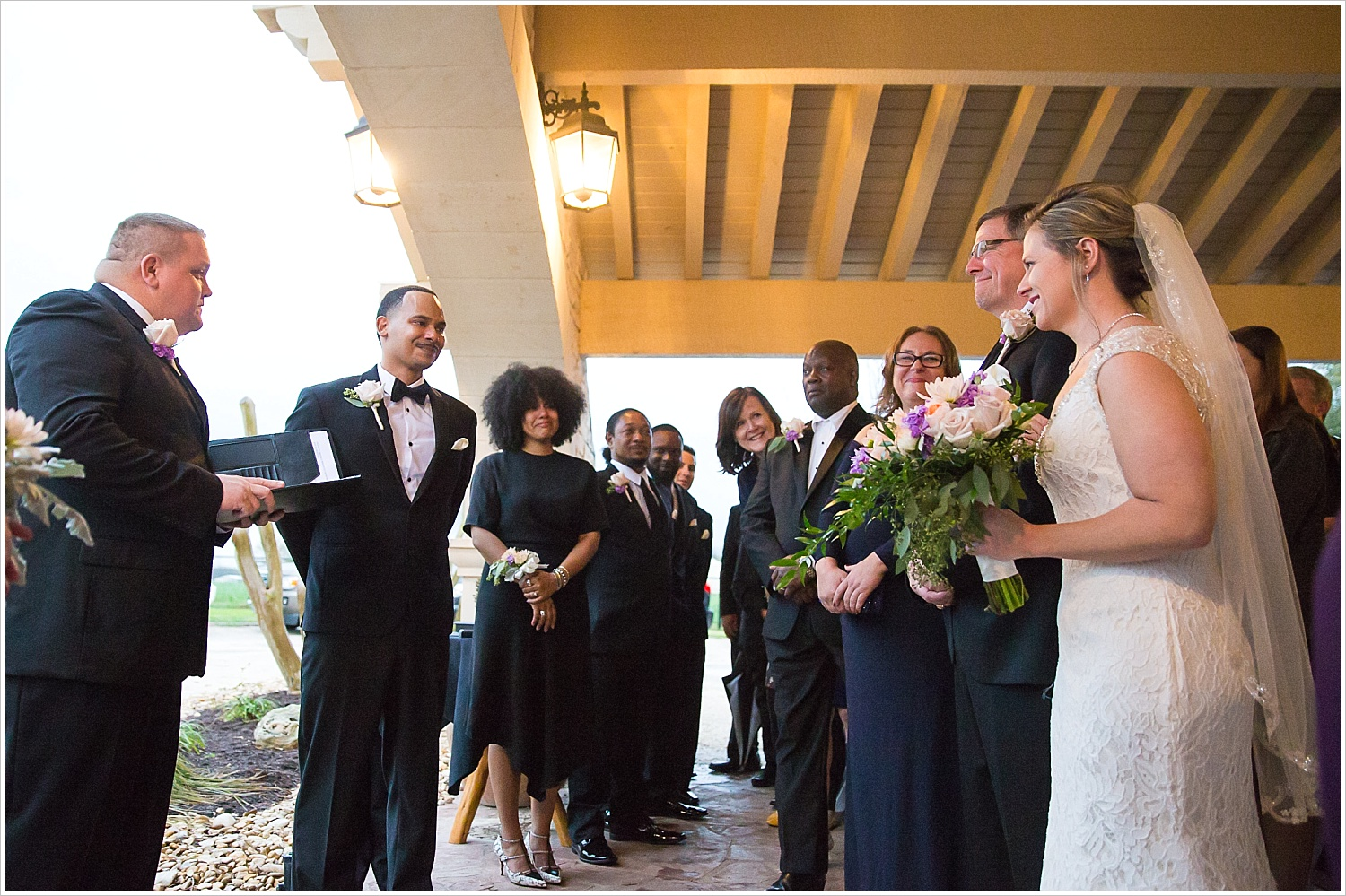 Groom's side smiles at bride coming down the aisle with her father