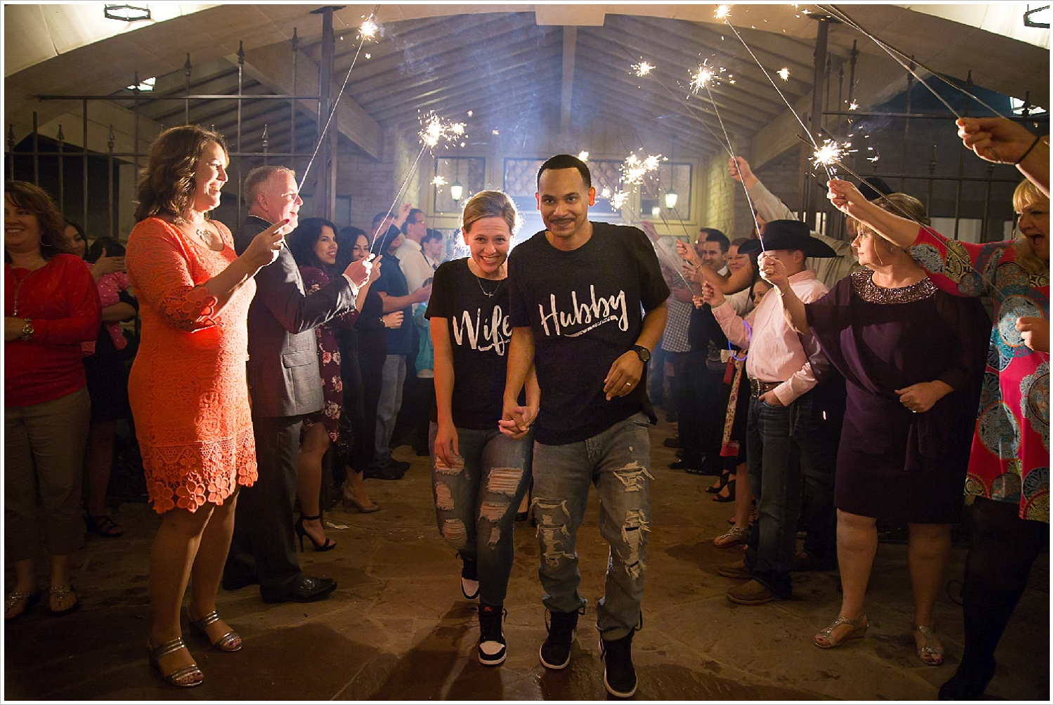 """Bride and groom run through sparkler exit wearing matching """"Hubby"""" and """"Wifey"""" shirts at the end of their La Rio Mansion wedding"""