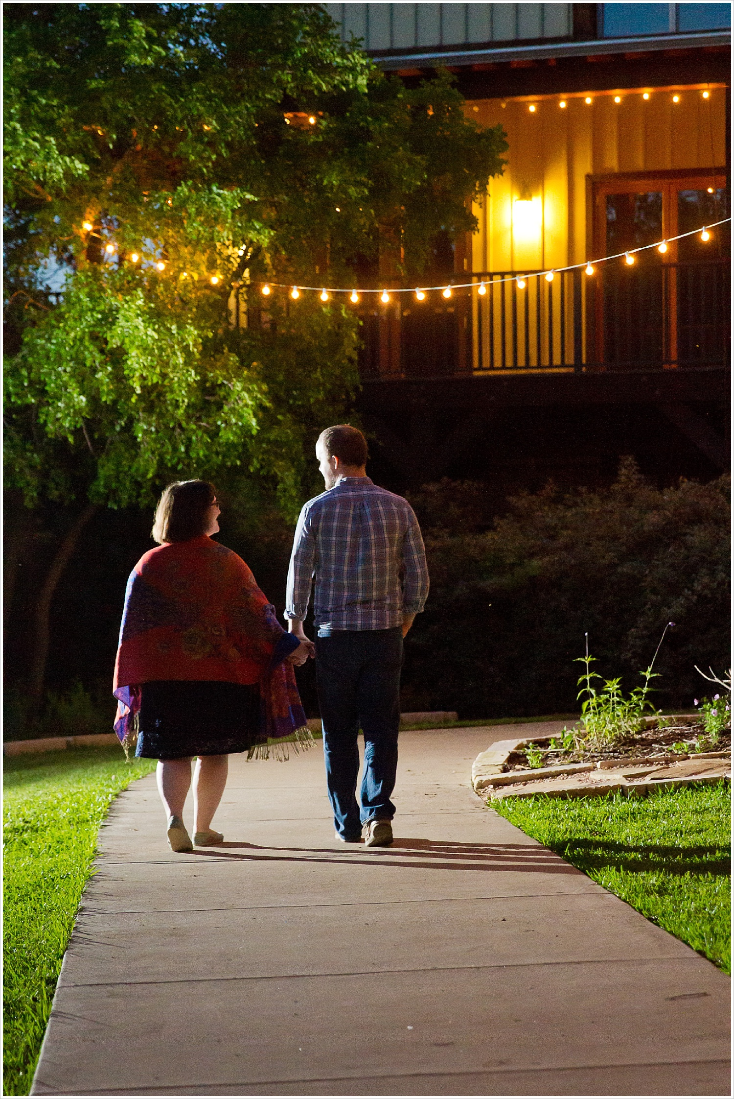 Couple walks away from camera, hand-in-hand, under string lights at Carleen Bright Arboretum in Woodway, Texas