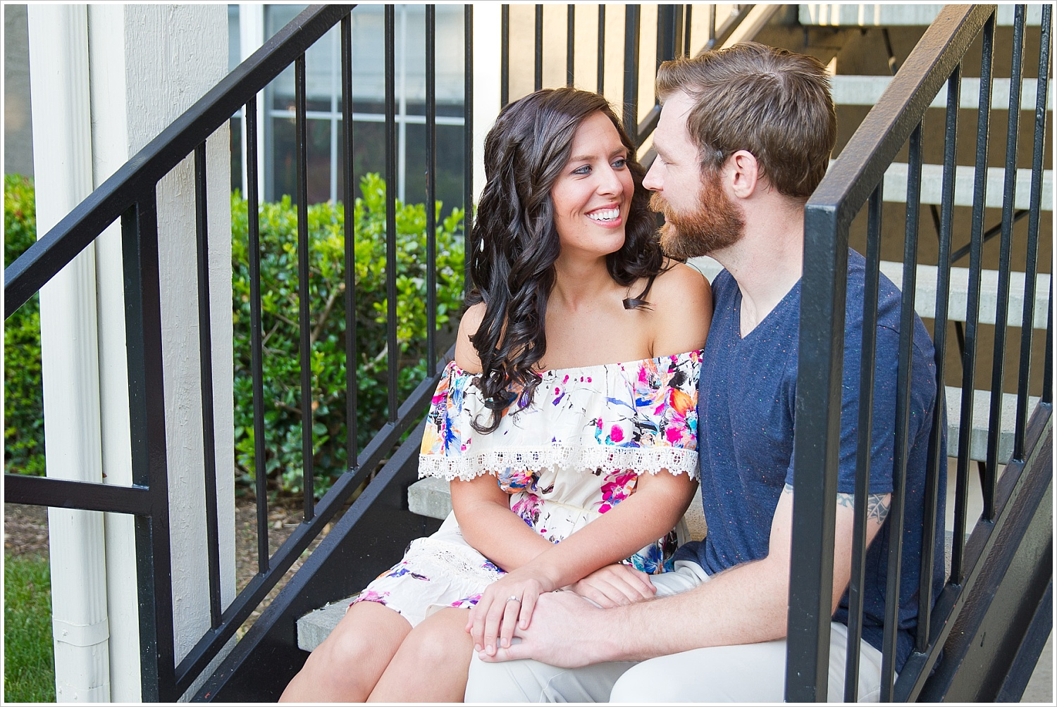 Randell & Fawn sit together on the stairs of their old apartment complex at an engagement photography session in Frisco, Texas by Texas wedding photographers Jason & Melaina Photography, www.jasonandmelaina.com
