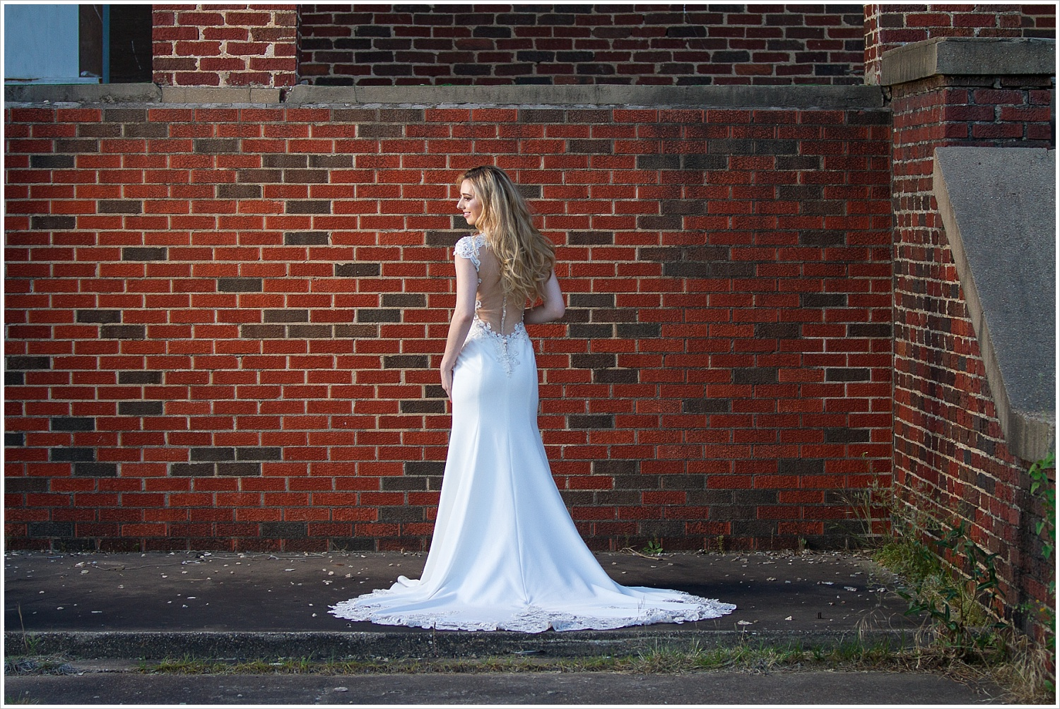 Model showcases open back and lace-trimmed train of _______ wedding gown in front of red brick wall at Rapoport Academy in Waco, Texas. Photography by Jason & Melaina Photography, Texas wedding photographers. www.jasonandmelaina.com