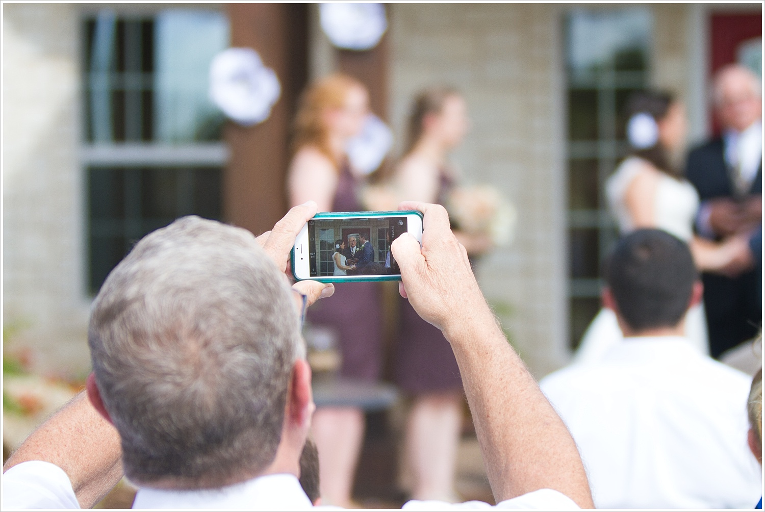 A wedding guest takes a picture of a bride and groom with his cell phone during a wedding ceremony-Should you have an unplugged wedding?, written by Texas Wedding Photographers, Jason & Melaina Photography-www.jasonandmelaina.com