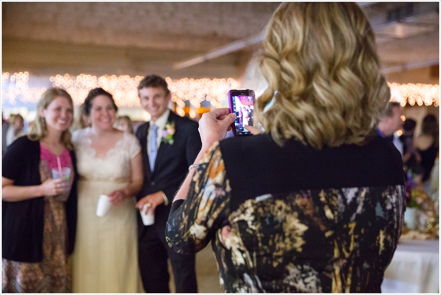 A wedding guest takes a picture of a bride and groom with her cell phone during a wedding reception-Should you have an unplugged wedding?, written by Texas Wedding Photographers, Jason & Melaina Photography-www.jasonandmelaina.com