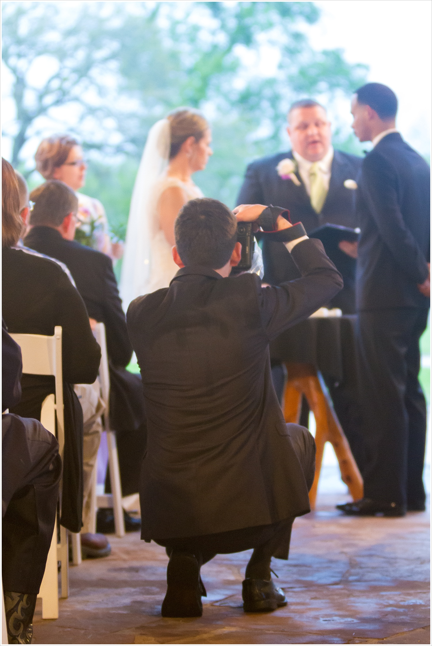 A photographer in the aisle during a wedding ceremony-Should you have an unplugged wedding?, written by Texas Wedding Photographers, Jason & Melaina Photography-www.jasonandmelaina.com