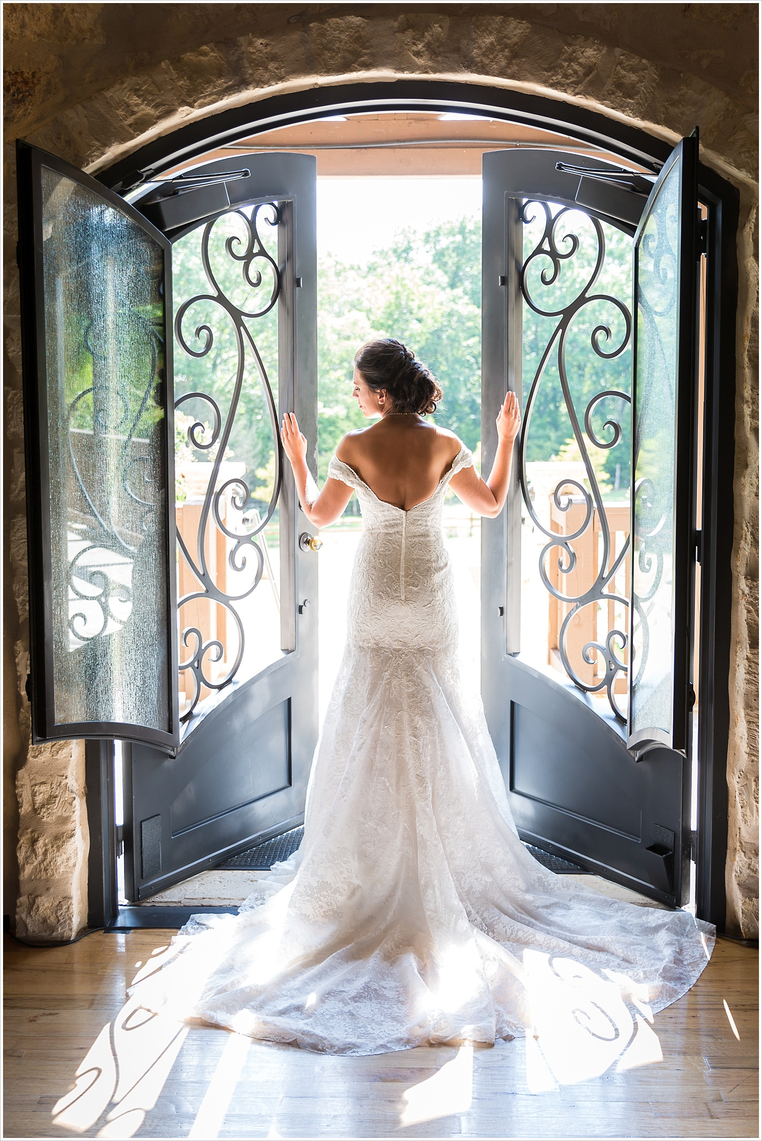 Bride poses by arched doorway, summer blush and navy wedding at Stone Hall at The Springs in McKinney, Texas, Jason & Melaina Photography, www.jasonandmelaina.com