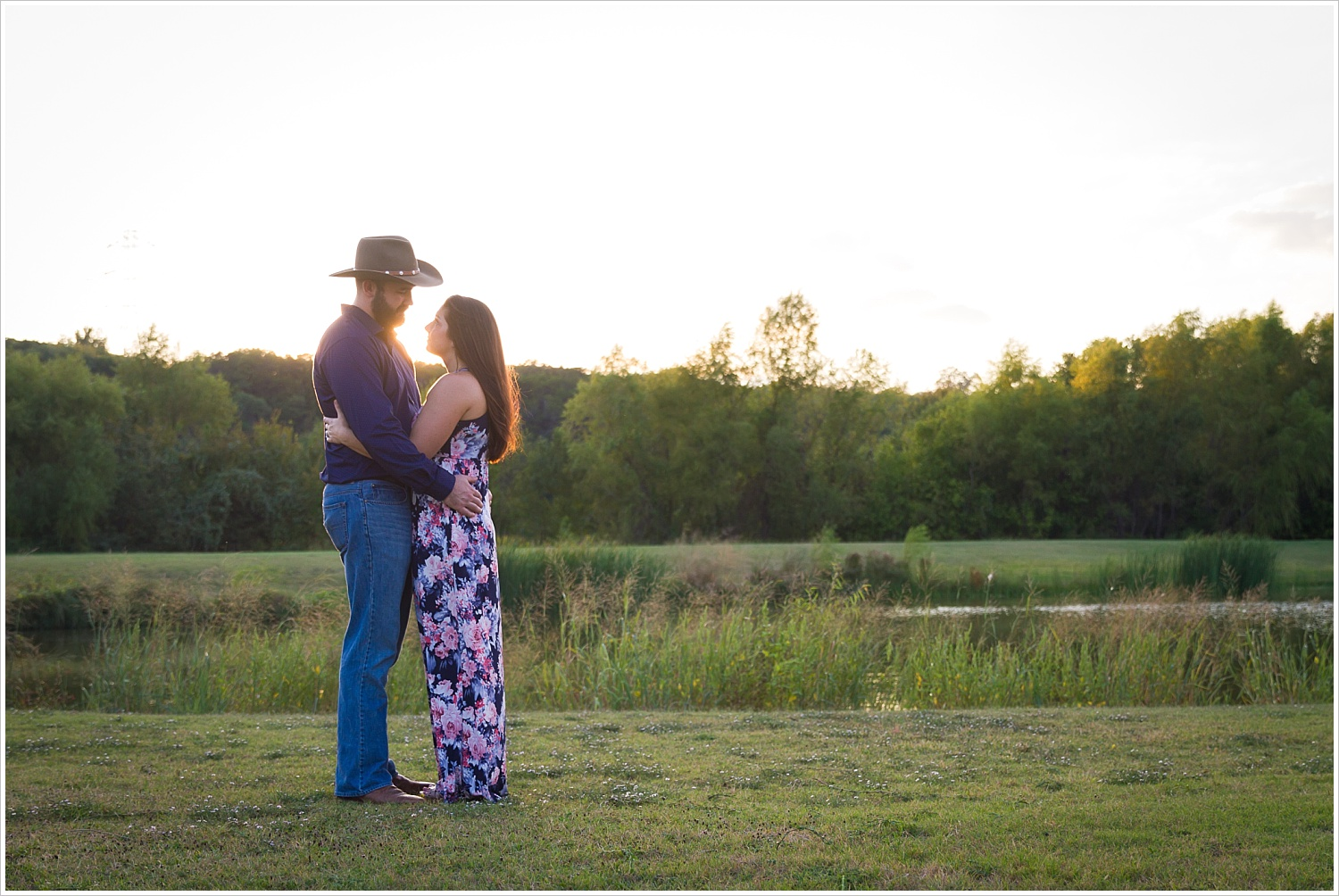 A couple holds one another with Texas sunset behind their faces during their engagement photo session in Waco, Texas, Jason & Melaina Photography - www.jasonandmelaina.com