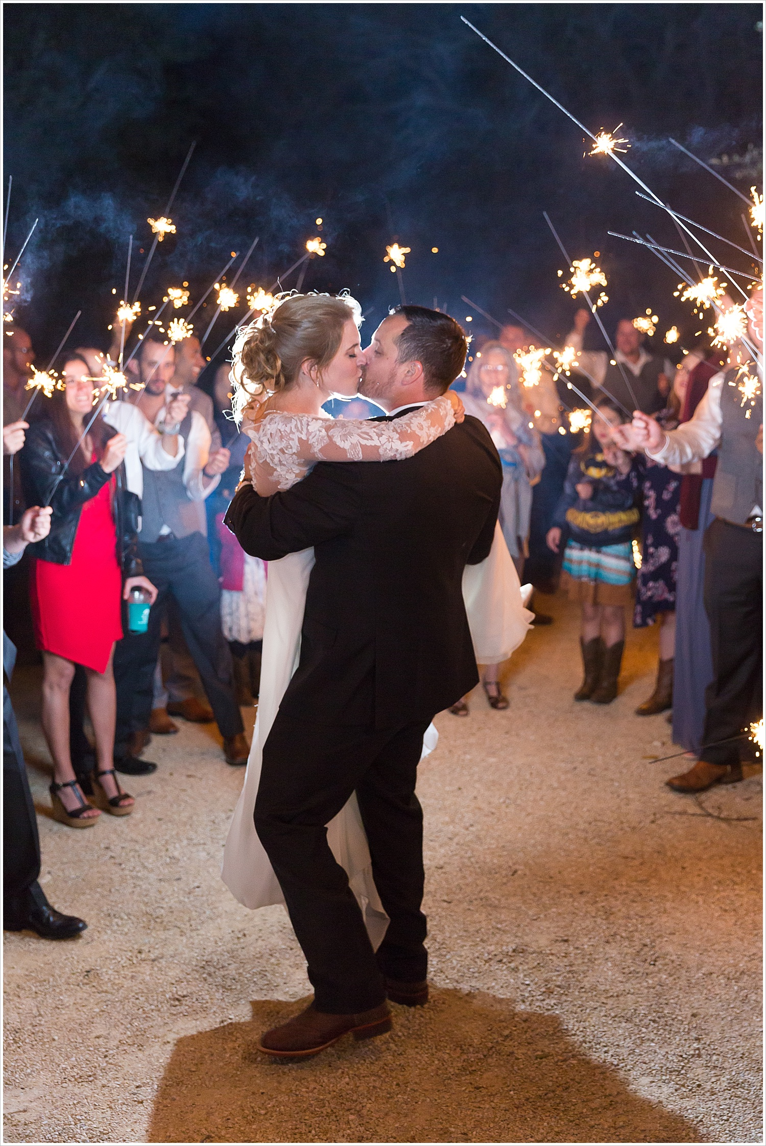 Groom carries his bride and kisses her during their sparkler exit at Bear Creek in Gatesville, Texas - Jason & Melaina Photography - www.jasonandmelaina.com