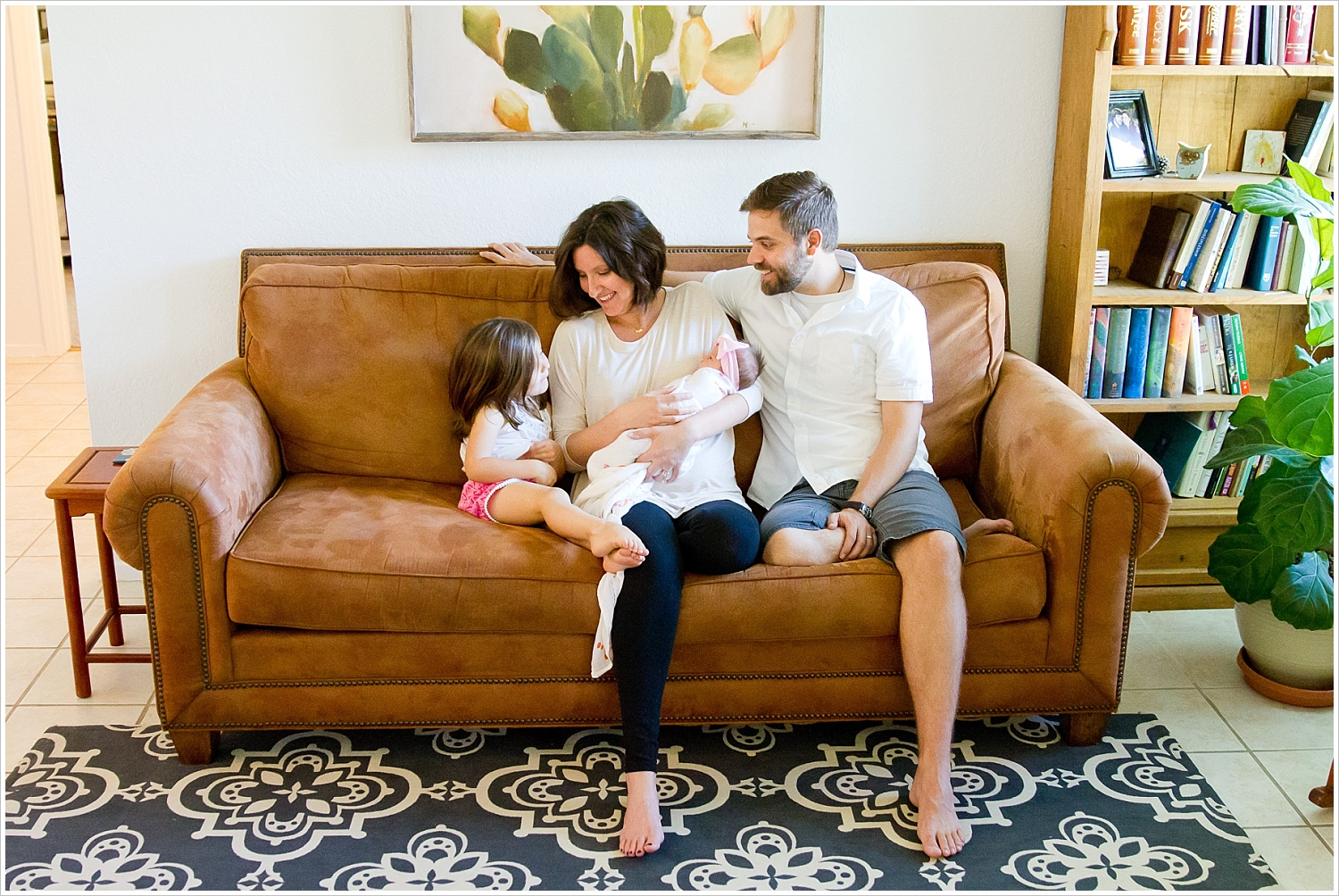 A mom and dad hold their newborn daughter while little sister looks on in their living room during a lifestyle in-home portrait session in Waco, Texas - Jason & Melaina Photography - www.jasonandmelaina.com