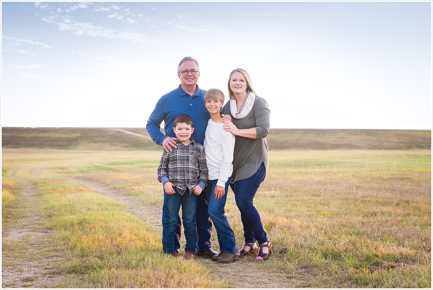 A family poses in a large field with an expansive Texas sky behind them in Waco, Texas - Jason & Melaina Photography - www.jasonandmelaina.com