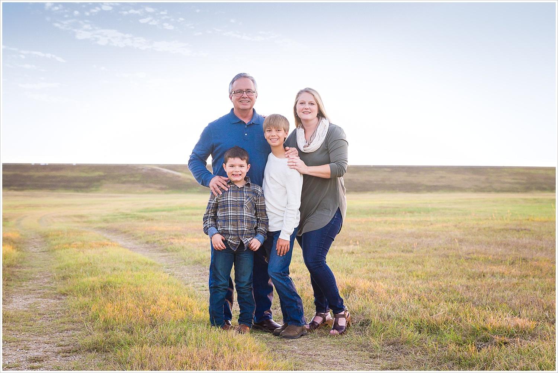 A family poses in a large field with an expansive Texas sky behind them in Waco, Texas - Jason & Melaina Photography - www.jasonandmelaina.com