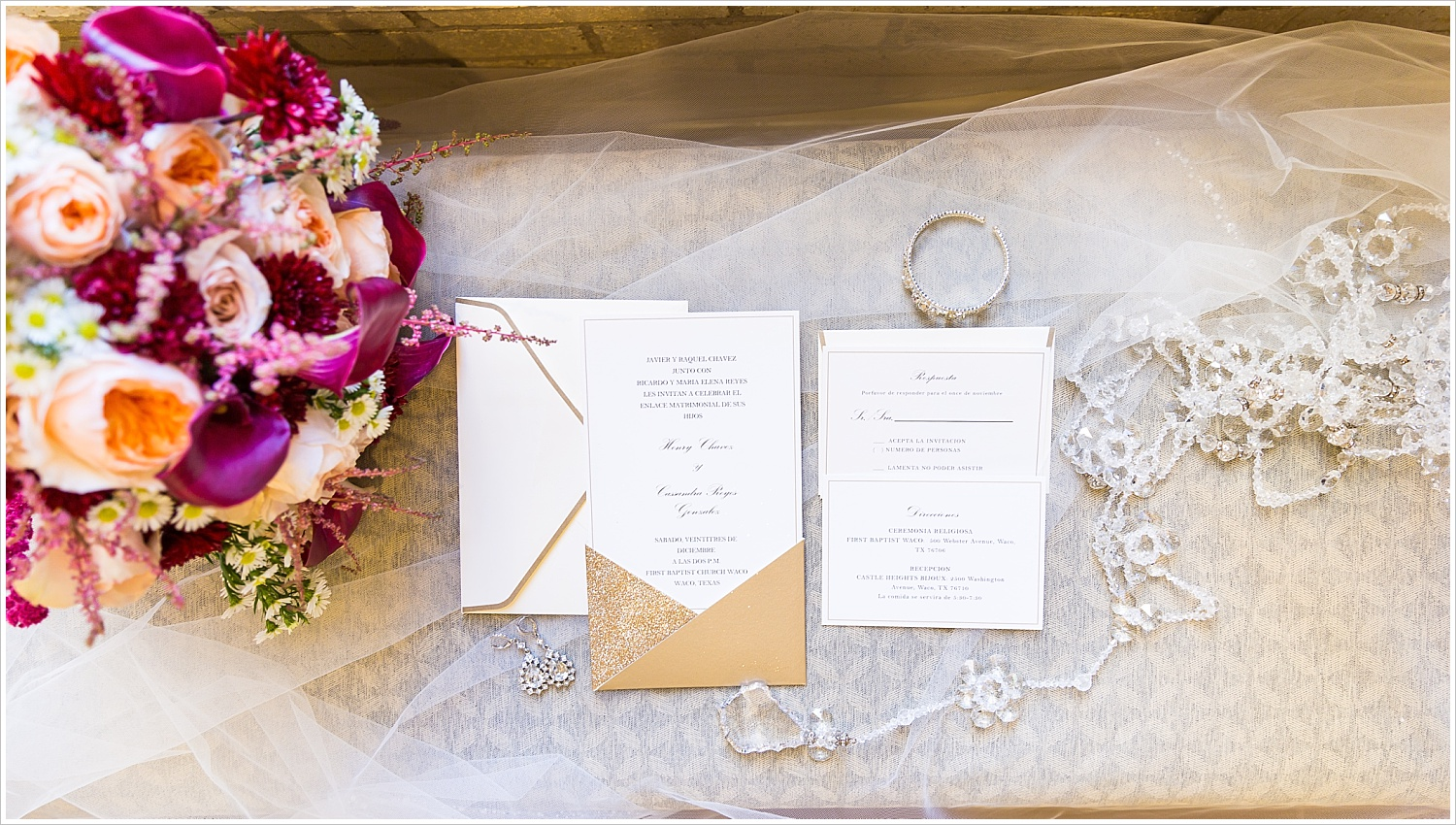 A calligraphy wedding invitation suite laid out on bride's veil, surrounded by bouquet and bride's jewelry - Jason & Melaina Photography - www.jasonandmelaina.com