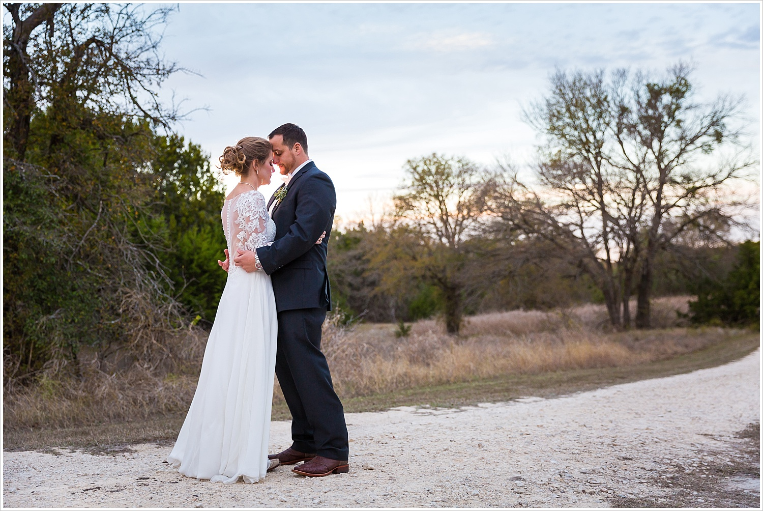 A groom and bride embraces with a sunset behind them on their wedding day at Bear Creek in Gatesville, Texas - Jason & Melaina Photography - www.jasonandmelaina.com