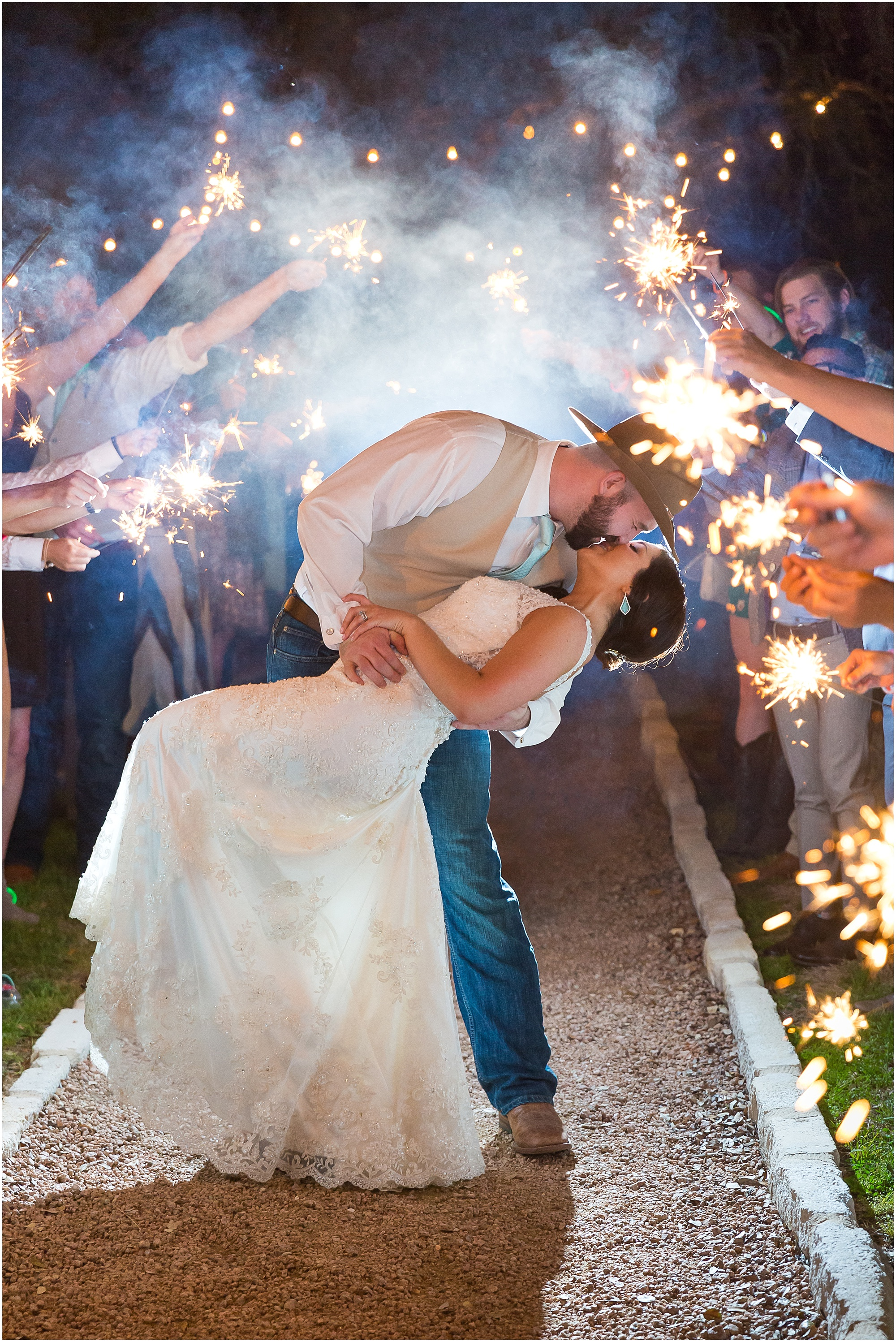 Groom dips bride and kisses her during their sparkler exit - Peacock River Ranch - Jason & Melaina Photography
