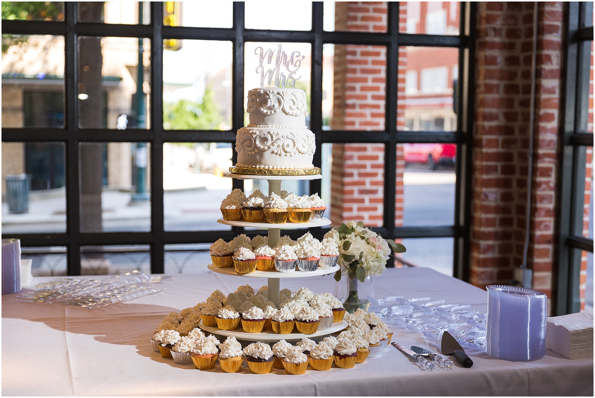 Cake and cupcake display at a warehouse wedding in Waco, Texas - www.jasonandmelaina.com
