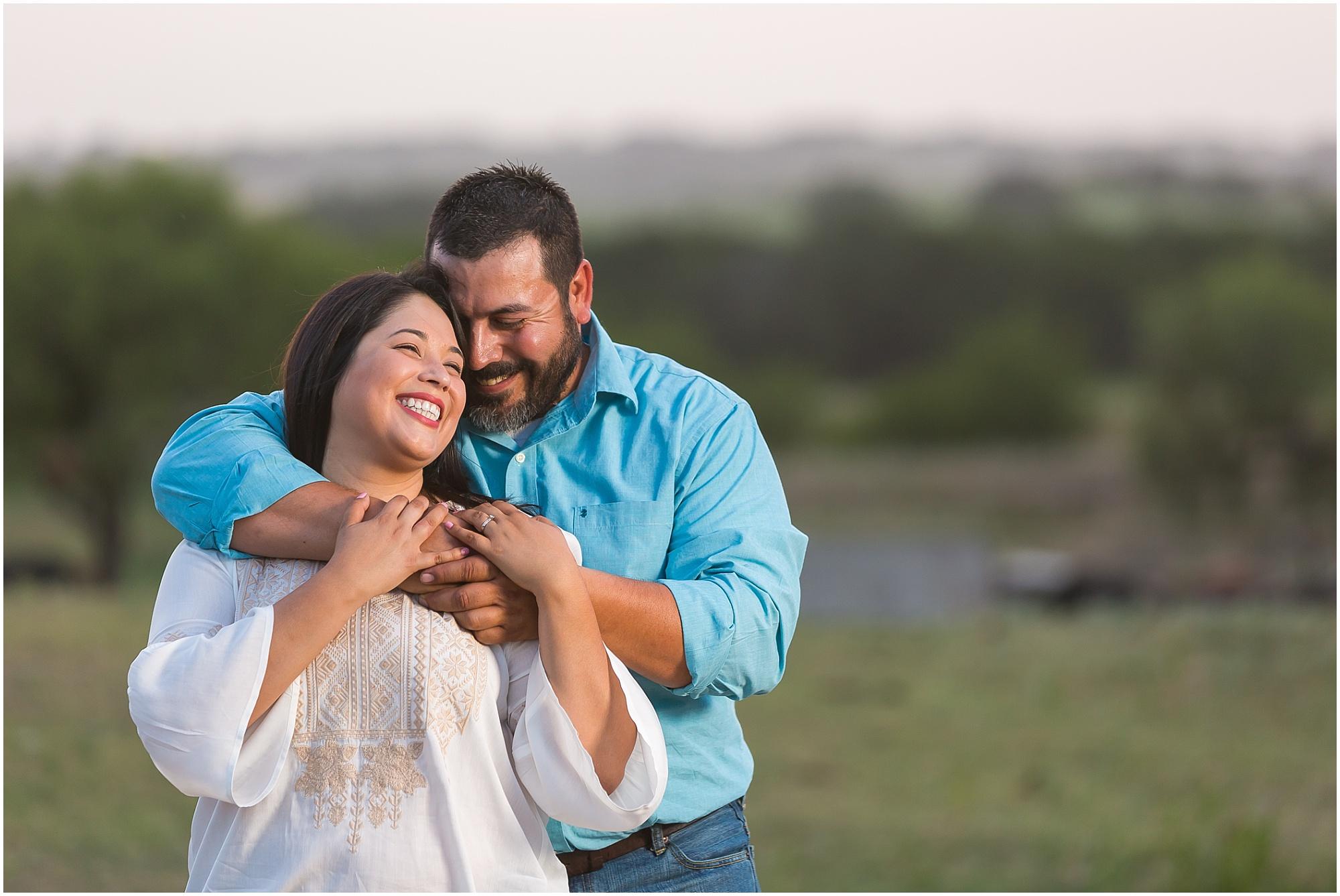 A couple laughs together while they hug, engagement portraits in Dublin, TX - Jason & Melaina Photography - www.jasonandmelaina.com