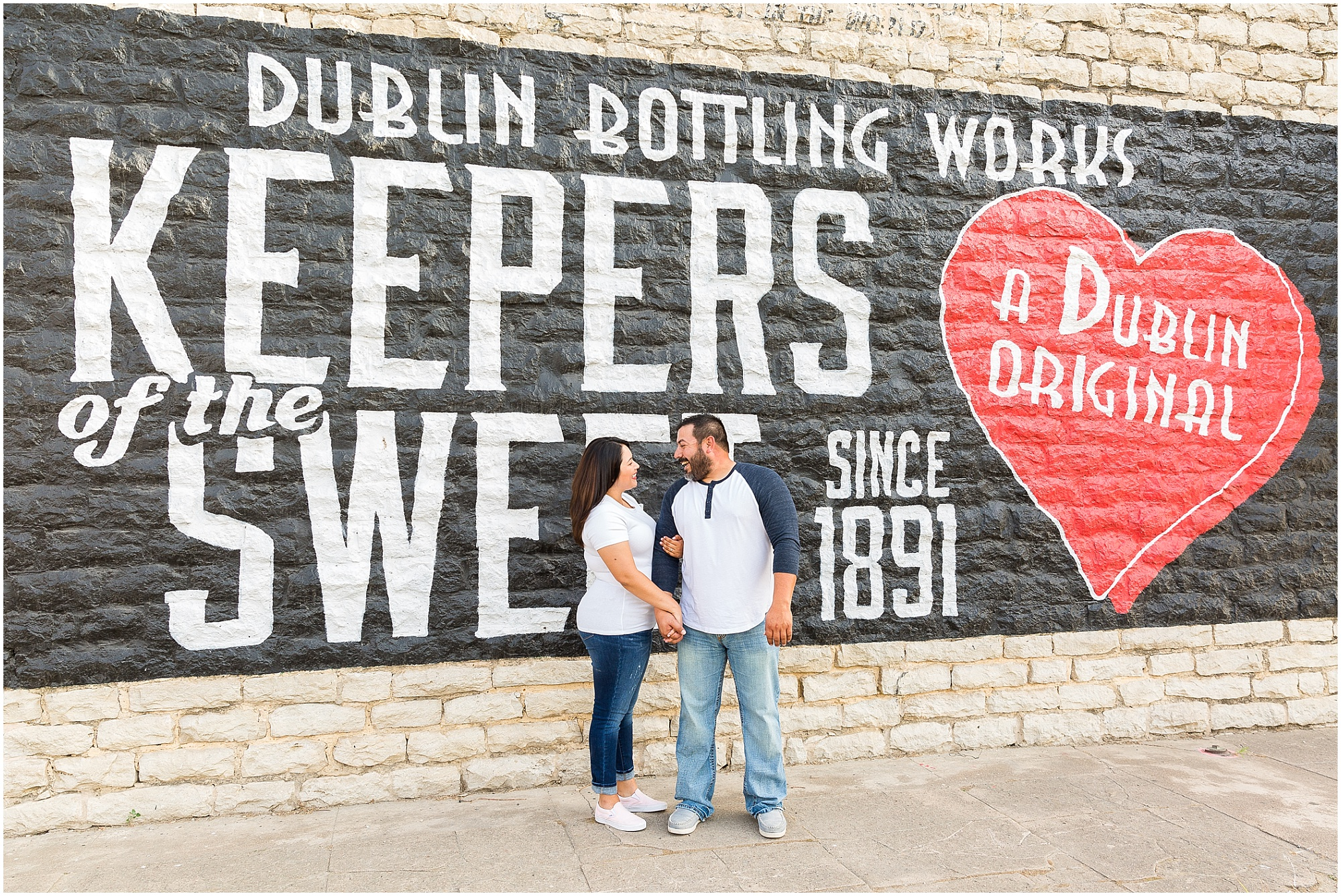 A couple stands in front of the Dr. Pepper mural downtown during their engagement portraits in Dublin, TX - Jason & Melaina Photography - www.jasonandmelaina.com