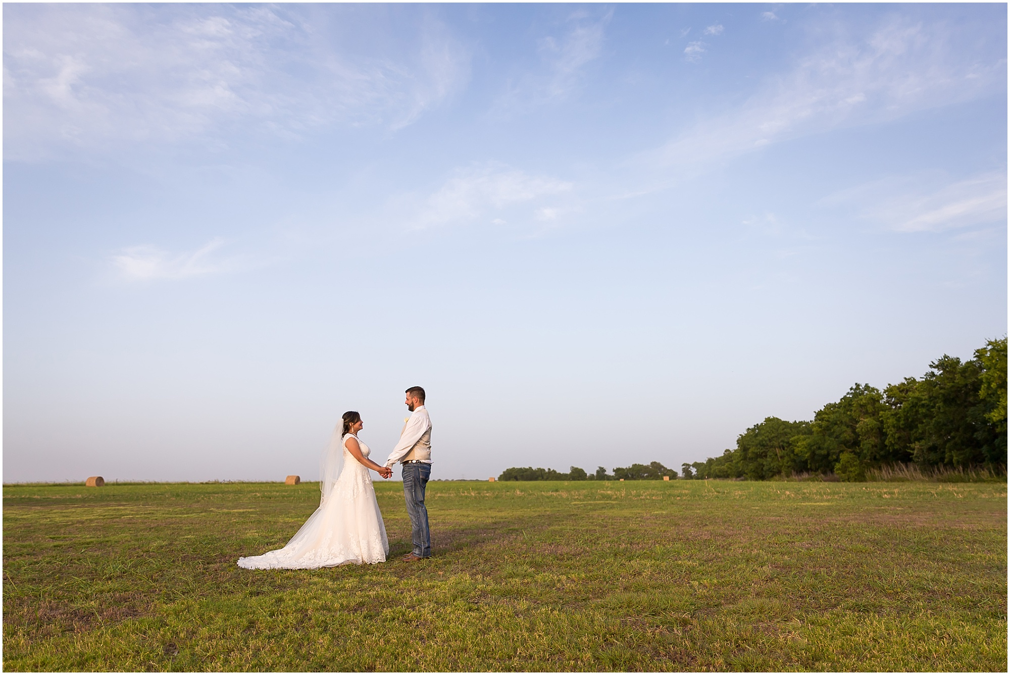 A bride and groom hold hands in a field with hay bales under a blue Texas sky at their rustic wedding in Belton, Texas - Jason & Melaina Photography - www.jasonandmelaina.com