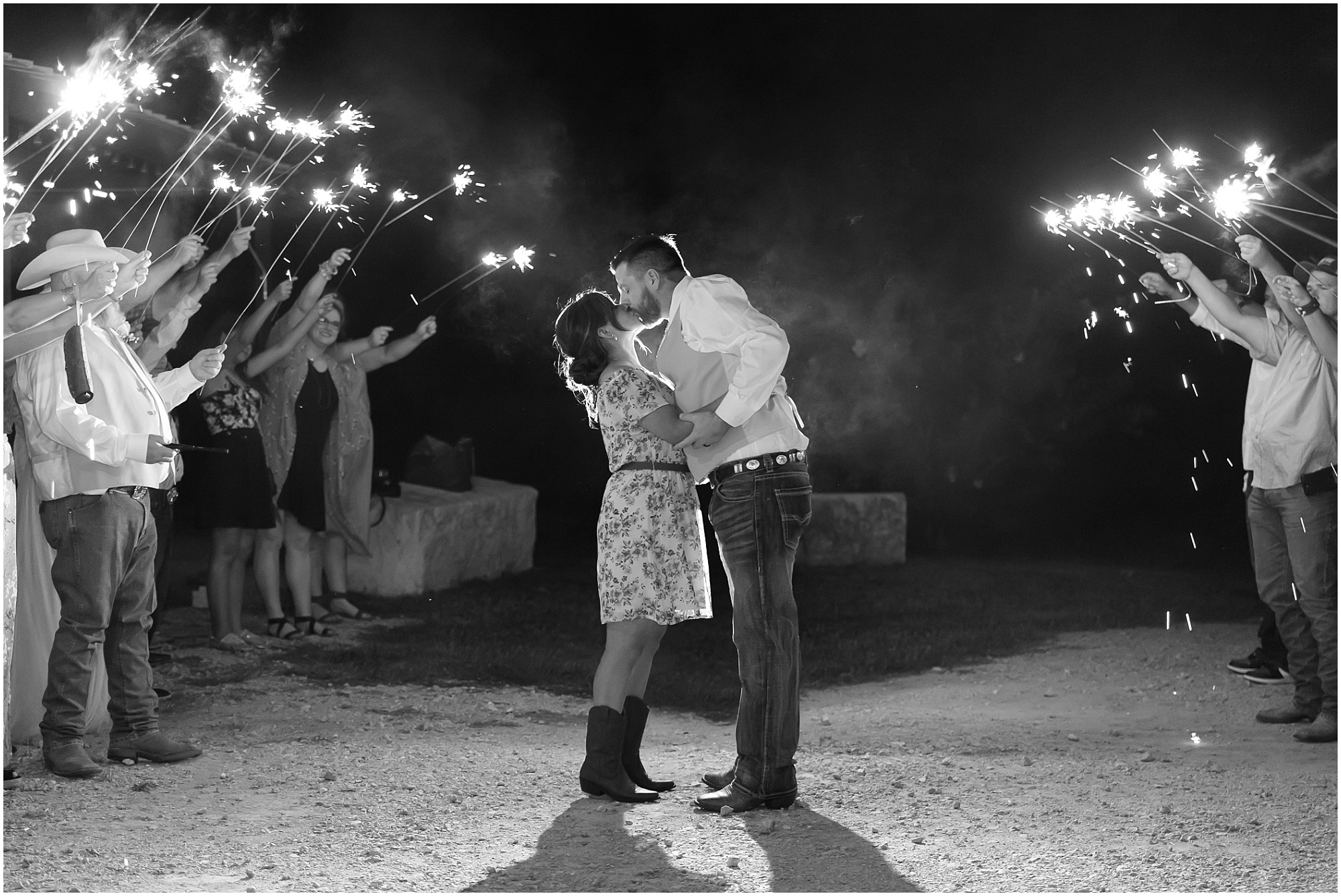 A bride and groom kiss surrounded by their guests with sparklers, black and white image - Rustic wedding at Rustic Acres in Belton, Texas - Jason & Melaina Photography - www.jasonandmelaina.com