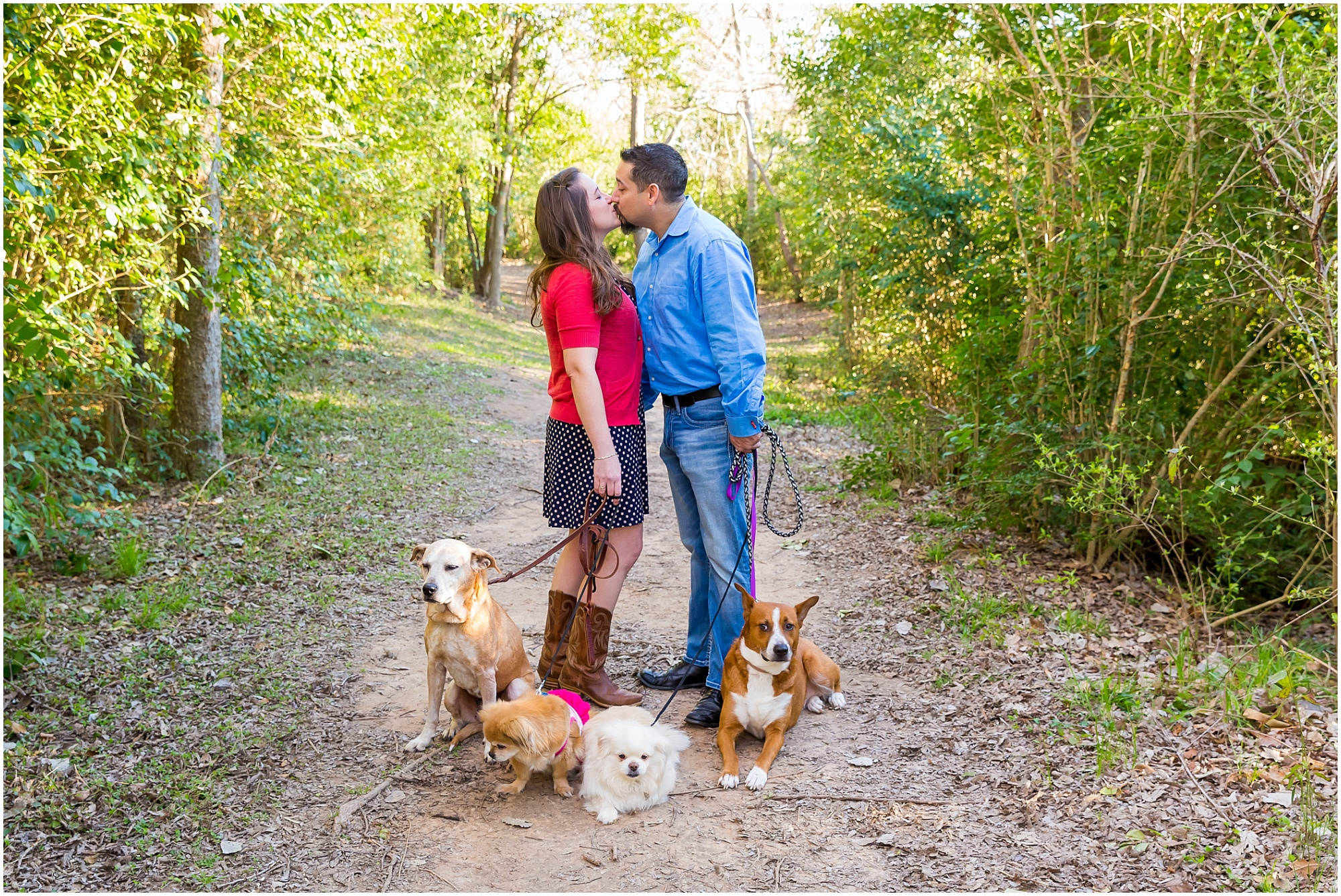 A couple kisses in the woods while walking their 4 dogs during their engagement portraits in Waco, Texas - Jason & Melaina Photography - www.jasonandmelaina.com