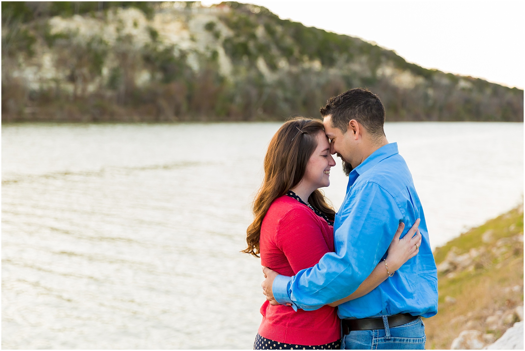 A couple nuzzles their faces together beside the Brazos River as the sun sets in Waco, Texas | Jason & Melaina Photography - www.jasonandmelaina.com