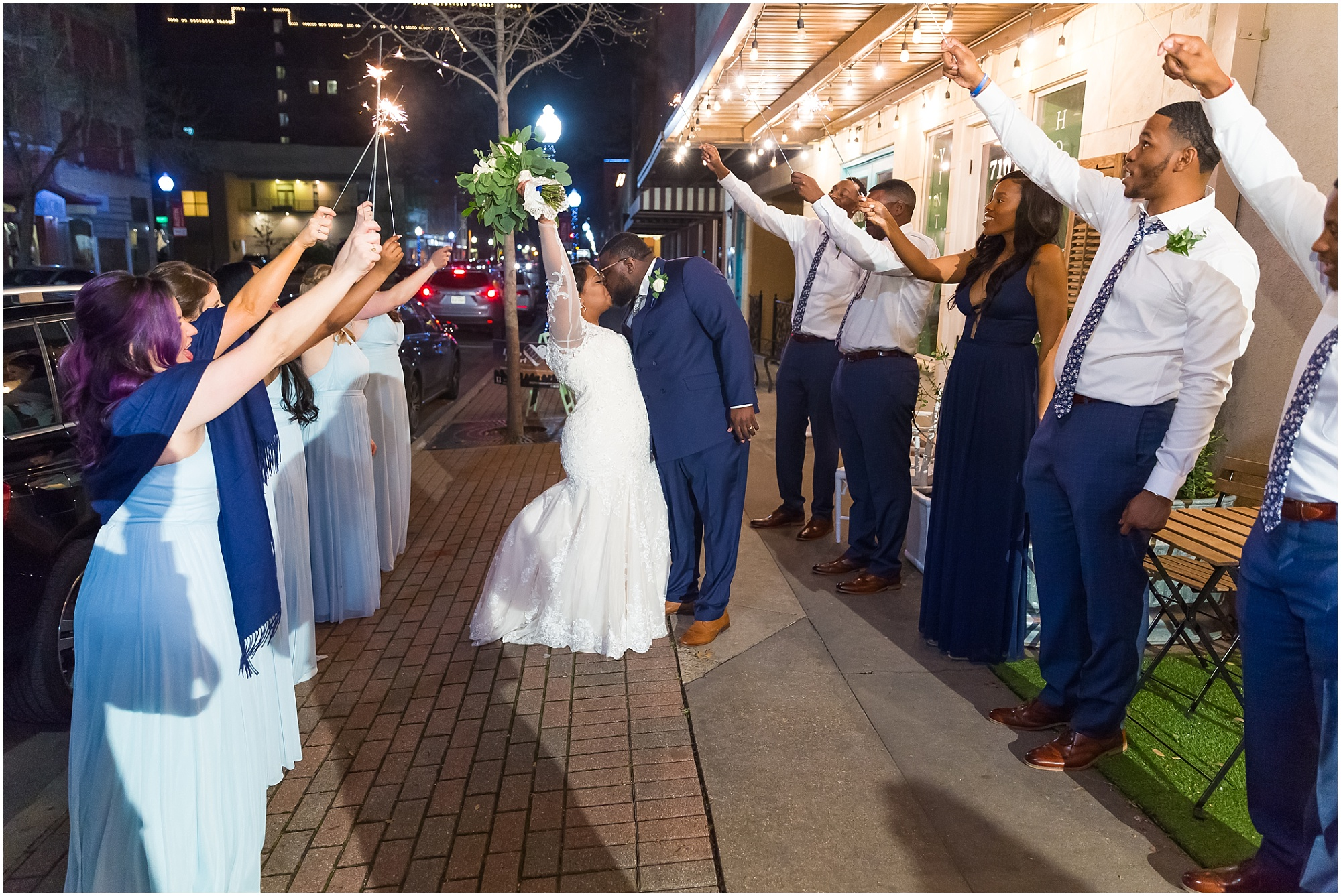 A bride and groom kiss under sparklers outside their reception at Cultivate 7Twelve in downtown Waco, Texas - Jason & Melaina Photography - www.jasonandmelaina.com
