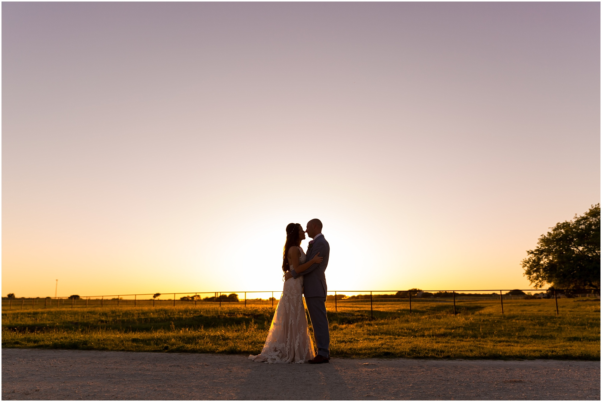 A bride and groom embrace with the Texas sunset behind them during their spring wedding day at Gathering Oaks Retreat in Crawford, Texas | Jason & Melaina Photography | www.jasonandmelaina.com