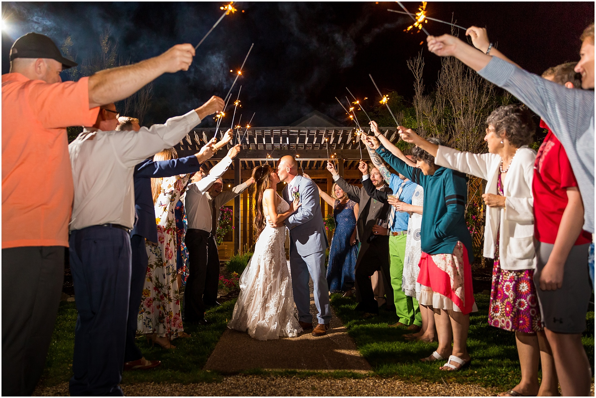 A bride and groom kiss under a tunnel of sparklers at the end of their wedding day | Jason & Melaina Photography | www.jasonandmelaina.com
