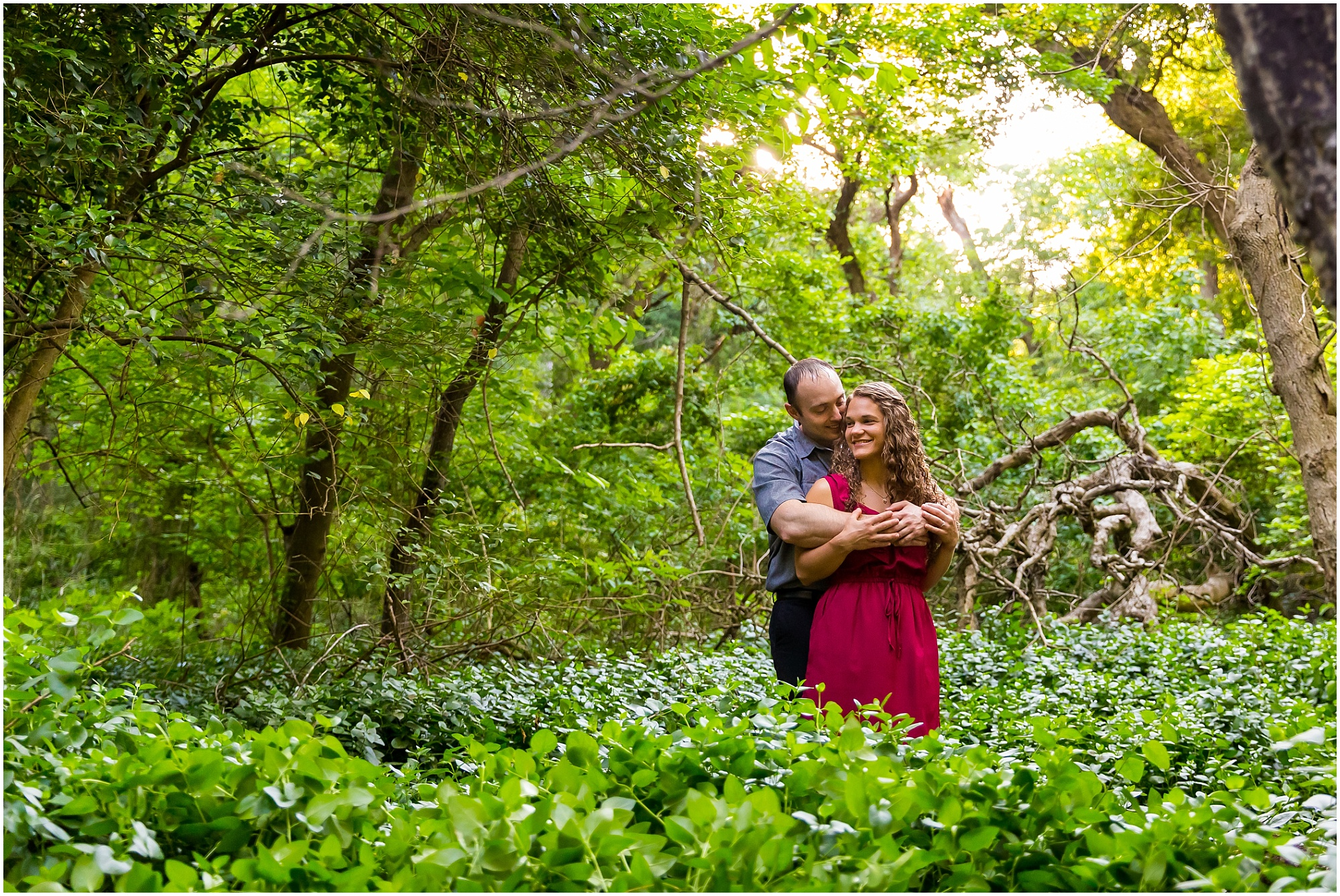 A man hugs his fiance from behind in a wooded trail inside Cameron Park in Waco, Texas - Jason & Melaina Photography - www.jasonandmelaina.com