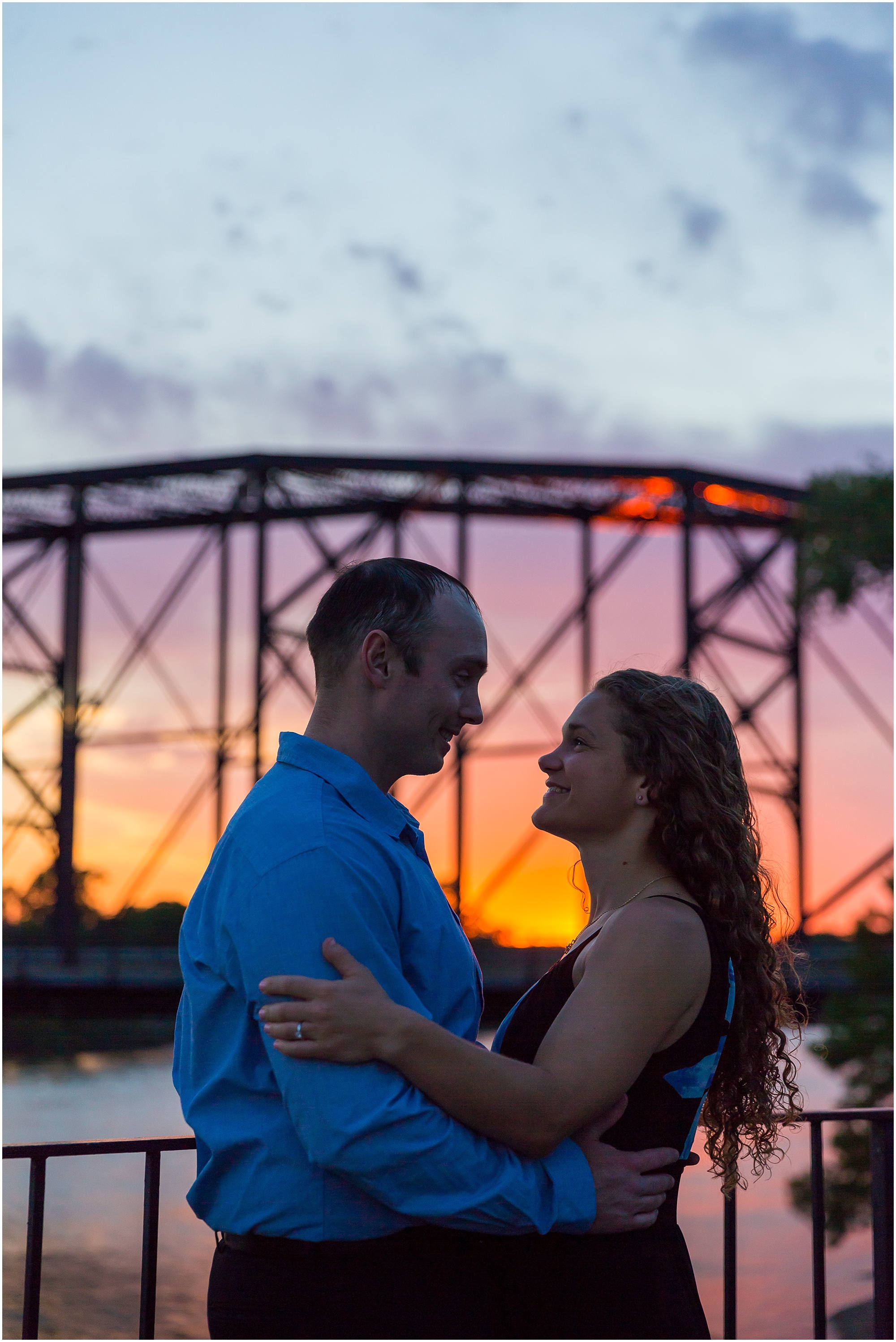 A couple stands on the MLK memorial platform by the Brazos River, looking into one another's eyes, while the sun sets behind them - Waco, Texas - Jason & Melaina Photography - www.jasonandmelaina.com