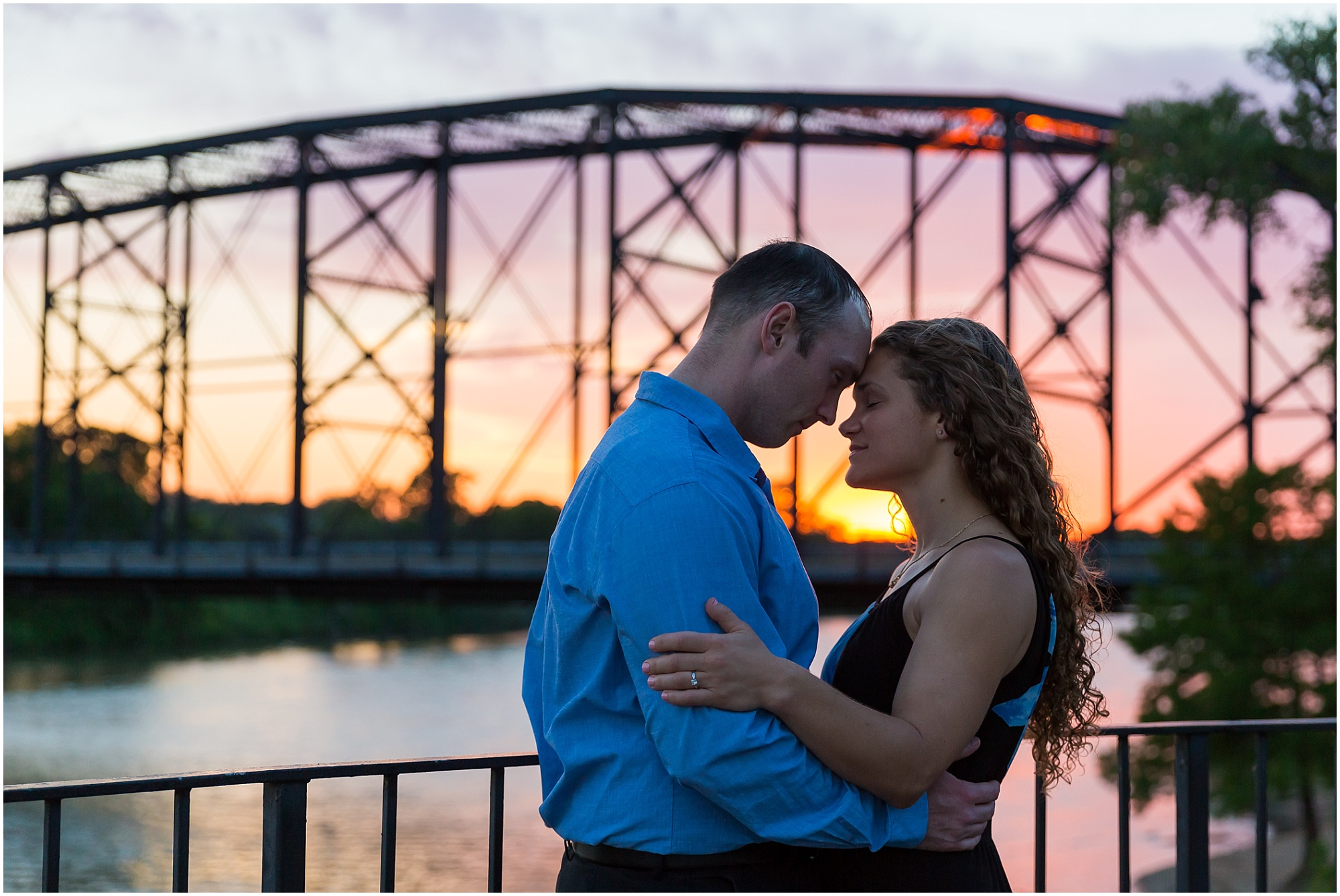 A couple puts their foreheads together with the sun setting behind them during their engagement photos near the Waco, Texas Suspension Bridge - Jason & Melaina Photography - www.jasonandmelaina.com